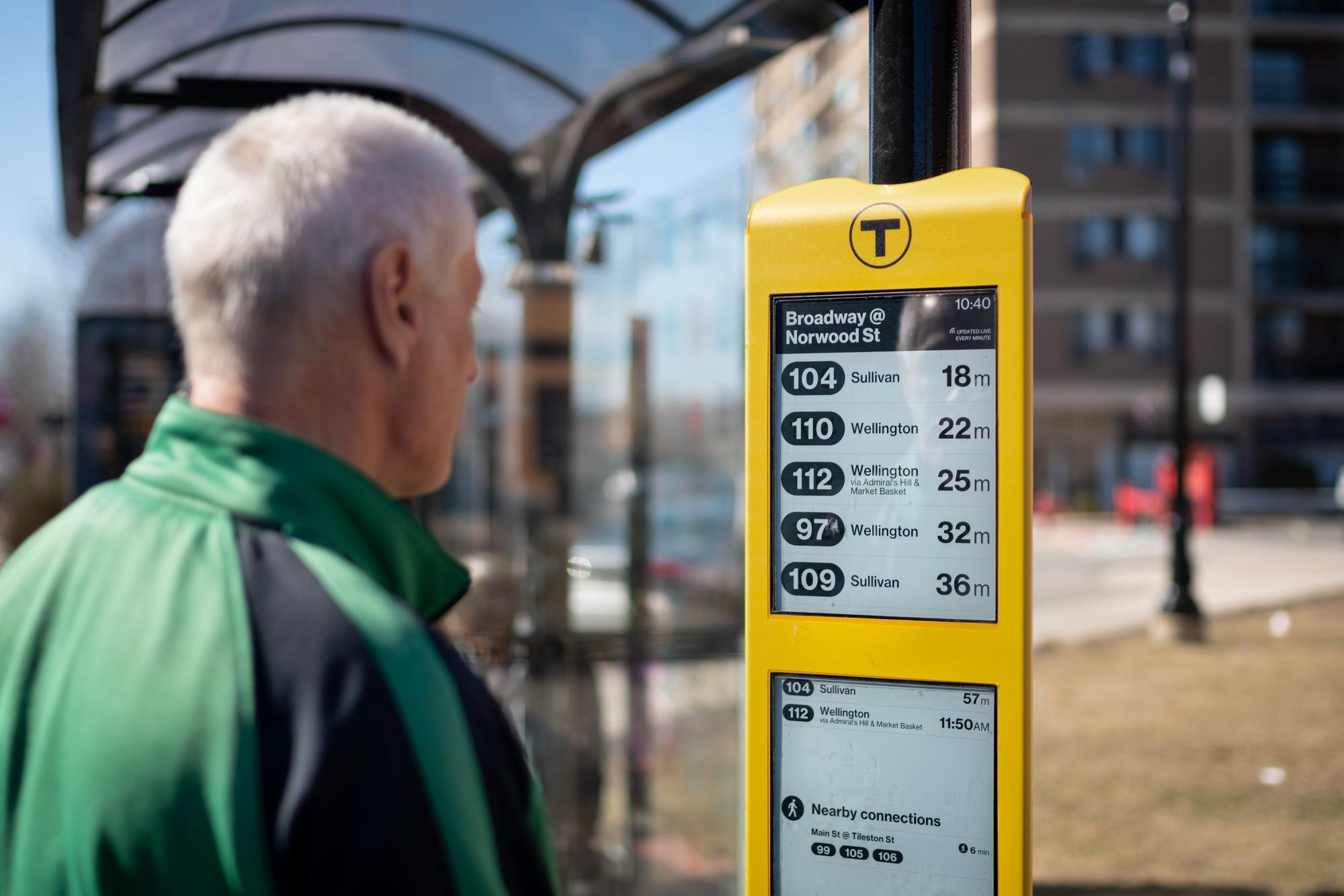 A rider reads the new E Ink sign at the Broadway bus stop in Everett