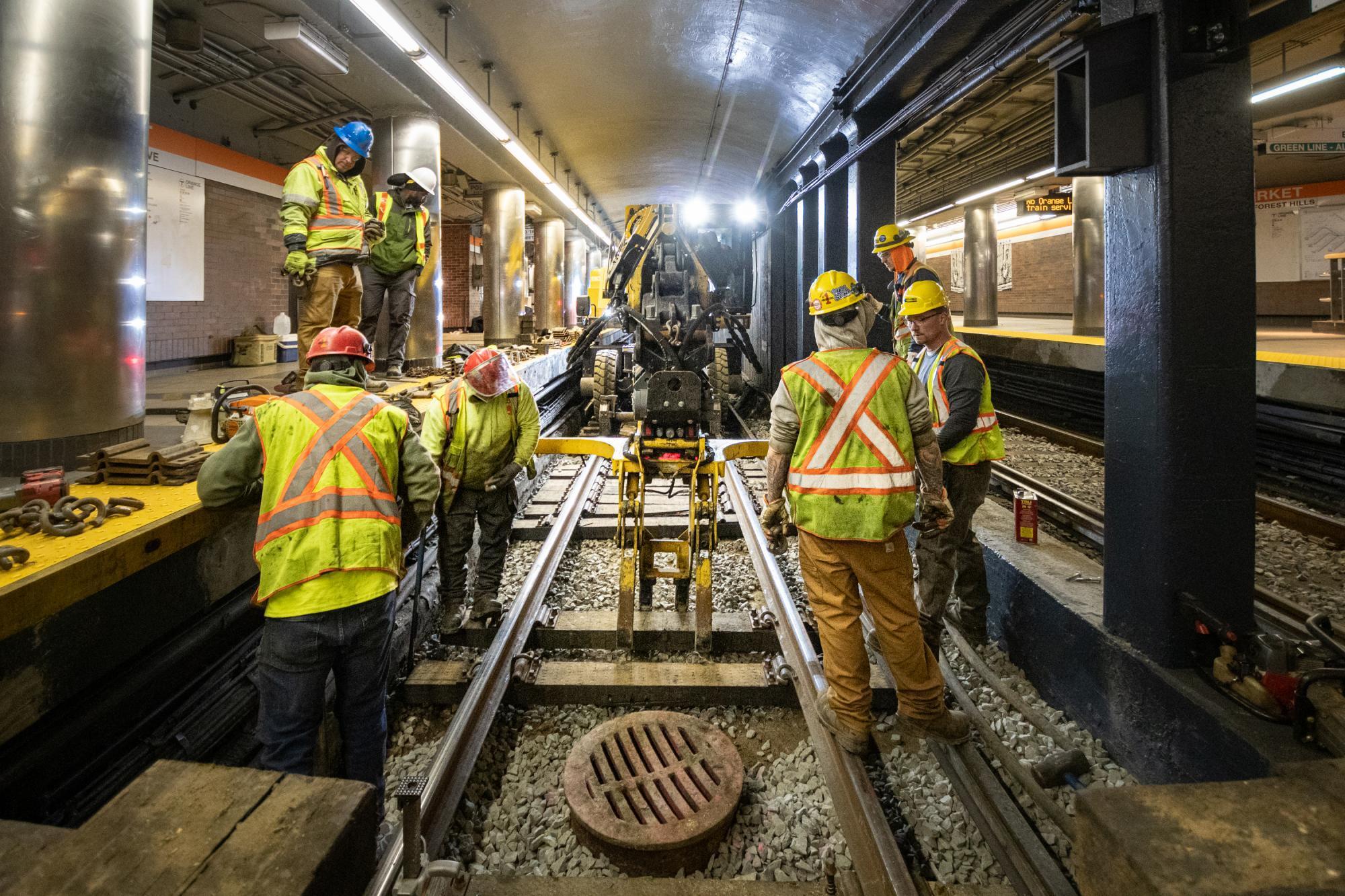 Crew members work on rail tie replacement during the final Orange Line weekend shutdown of winter 2020