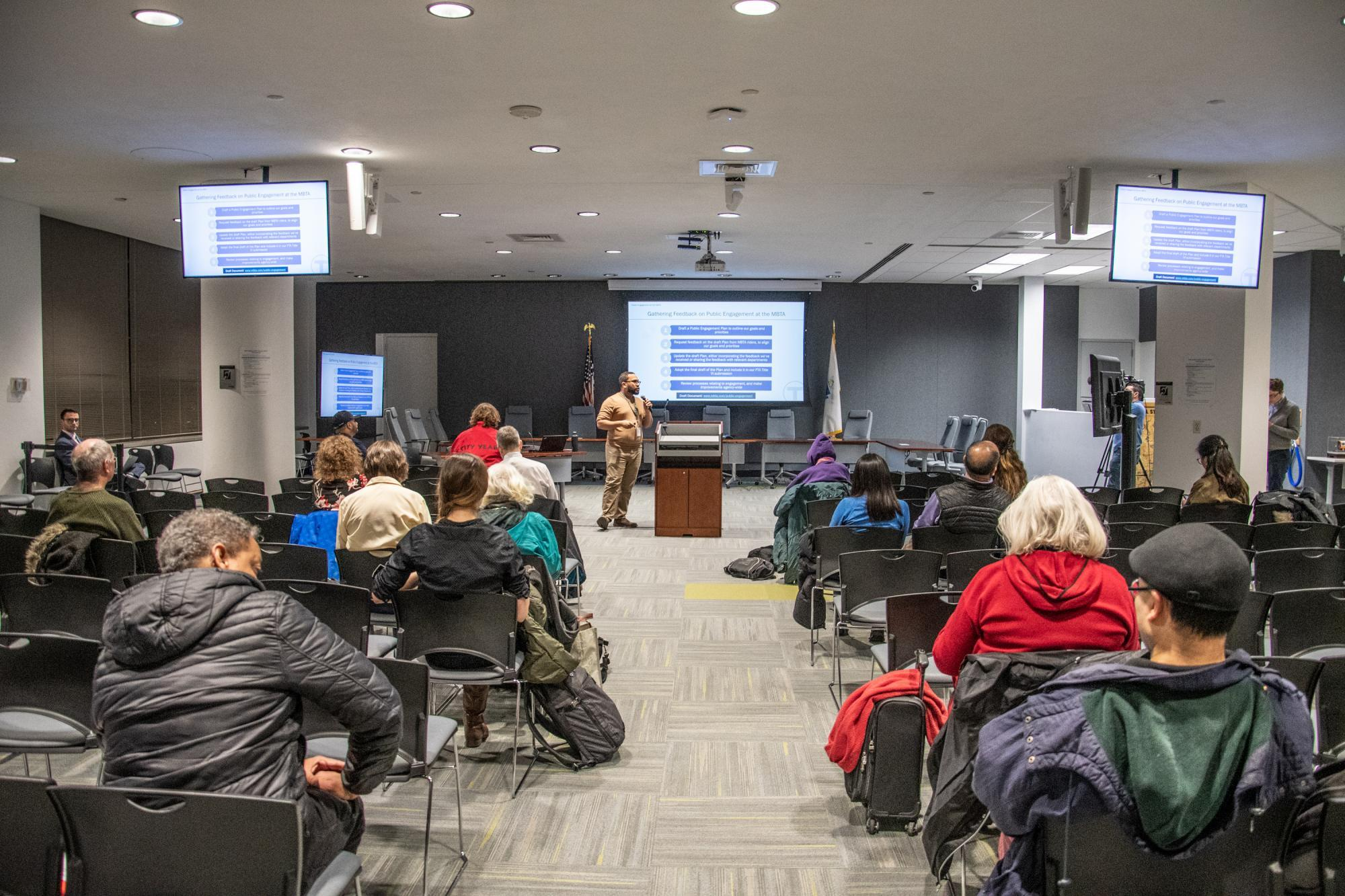 Community members at a public meeting at the State Transportation Building, with 3 screens showing meeting presentation slides and a speaker at the front.