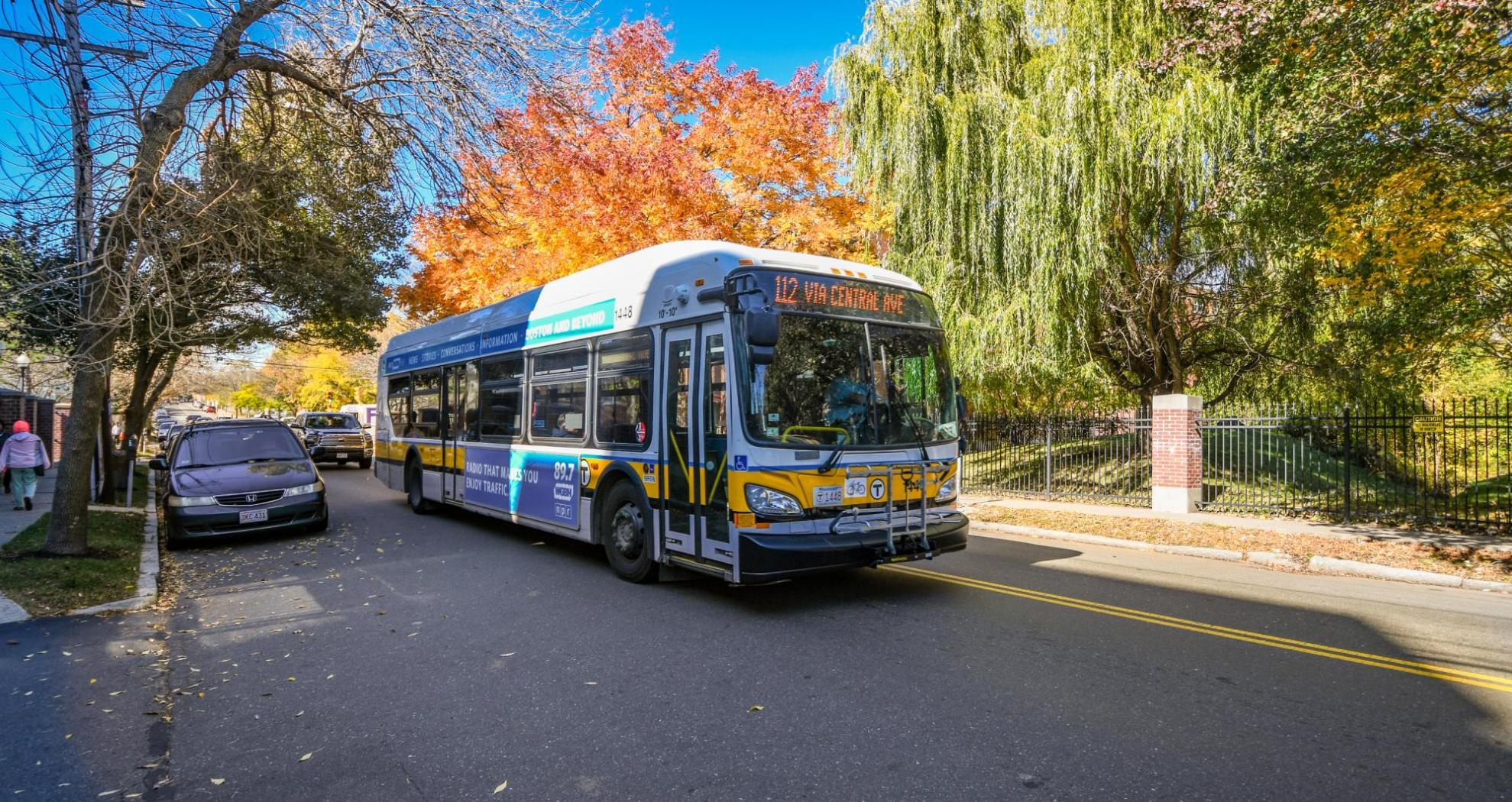 "Route 112 bus with a headsign that says ""Via Central Ave"" travels through Chelsea, with fall foliage in the background"