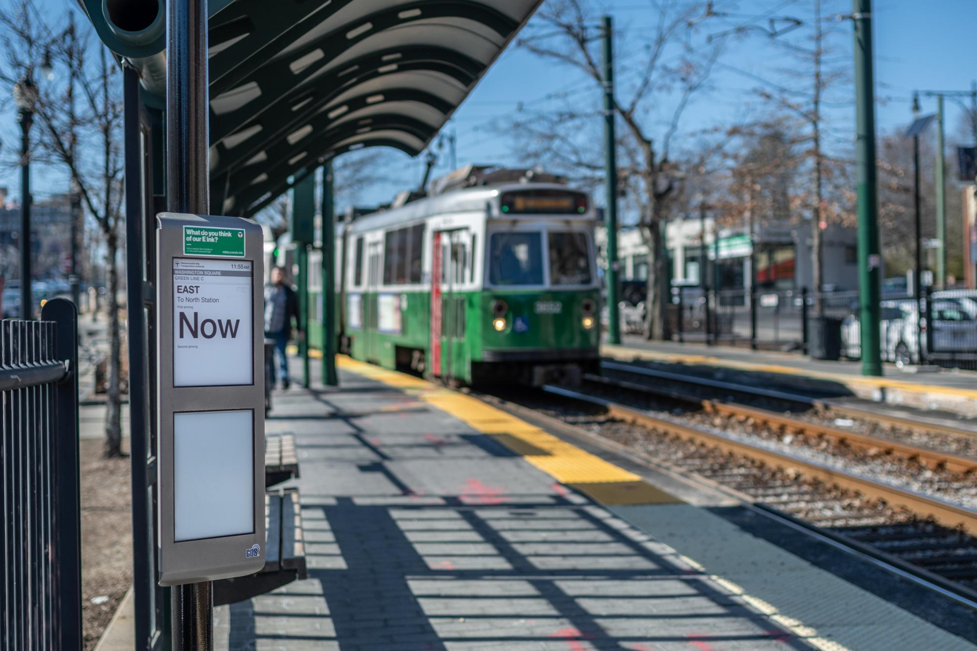 """A Green Line C train approaches the Washington Square inbound stop, with an e-ink sign saying """"Now."""""""