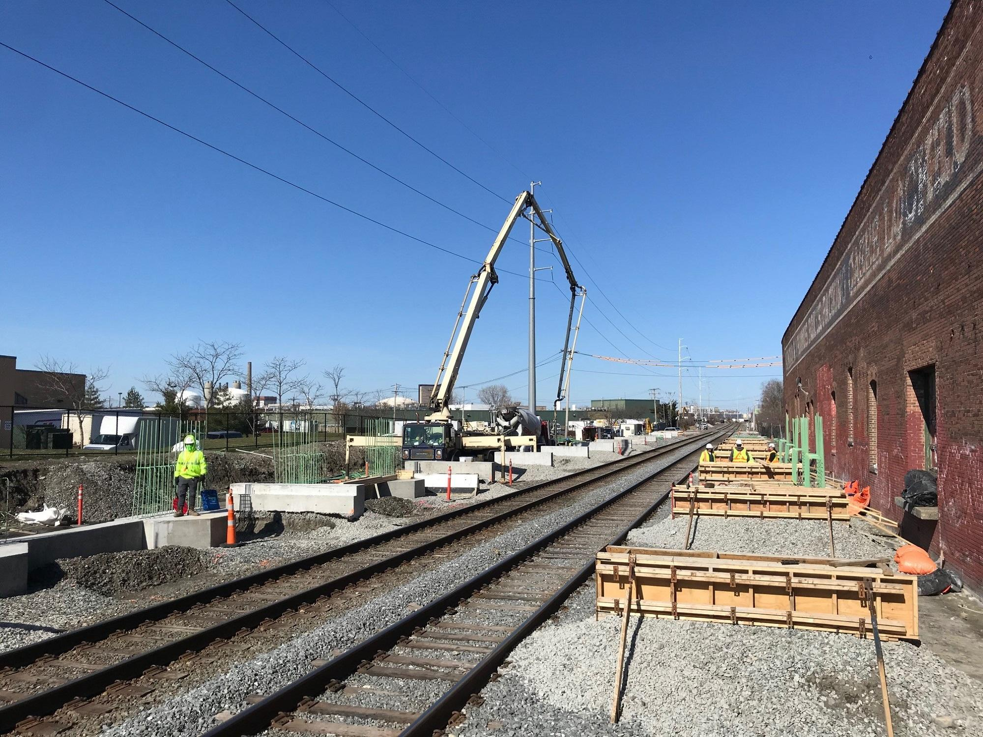 Crew members place concrete for Track 2 pile caps and canopy bases at Chelsea Commuter Rail Station, April 2020