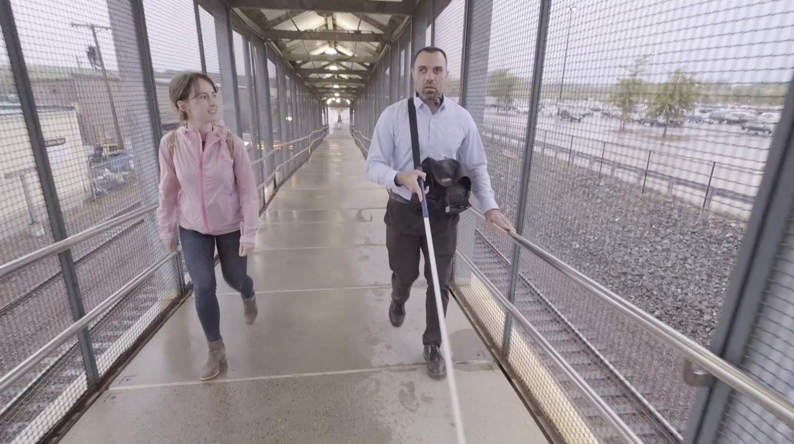 A CTD employee walks with a rider during a user research study for blind and low vision riders