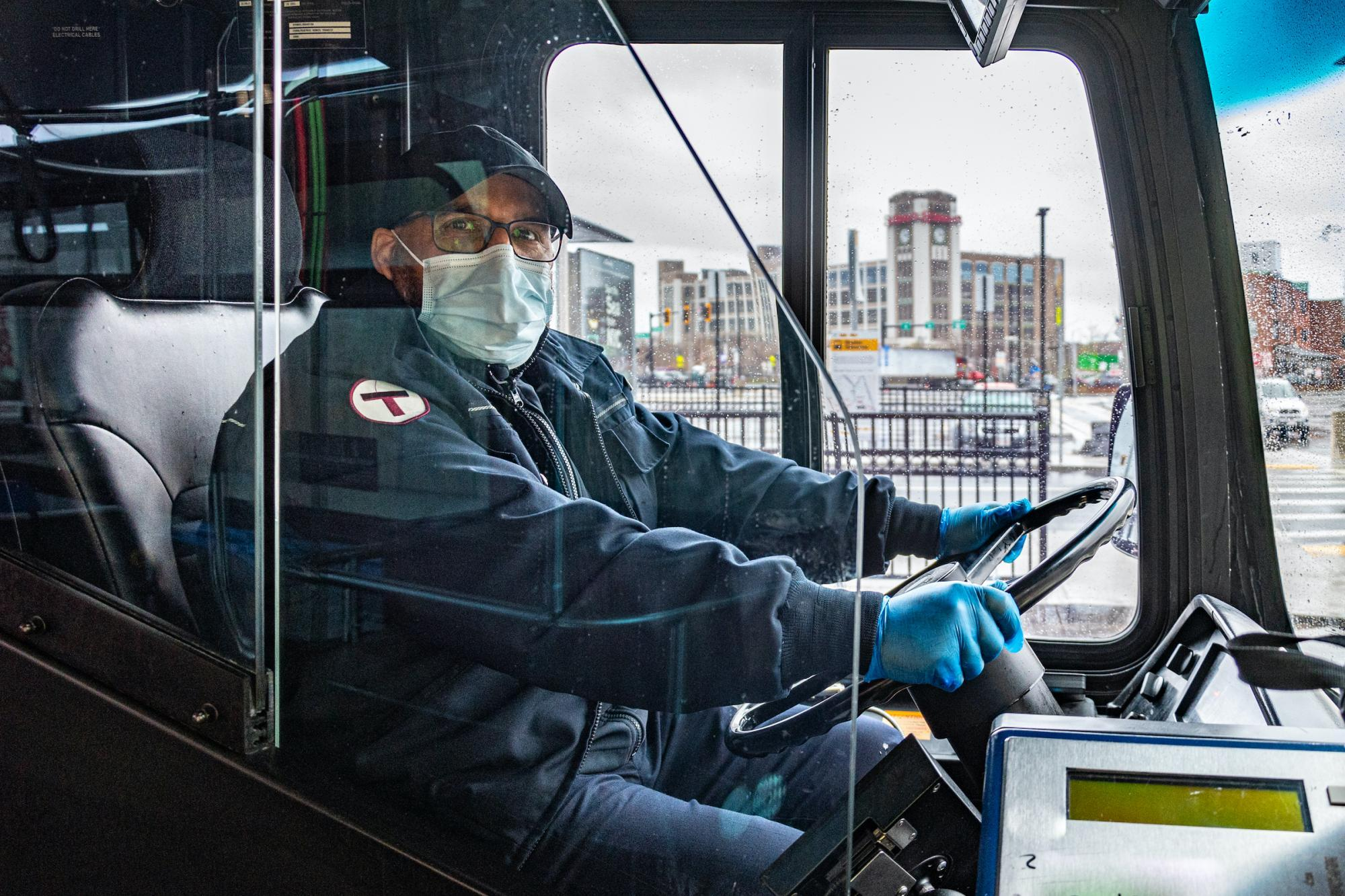 Operator driving bus at Sullivan Square, wearing a face covering and gloves