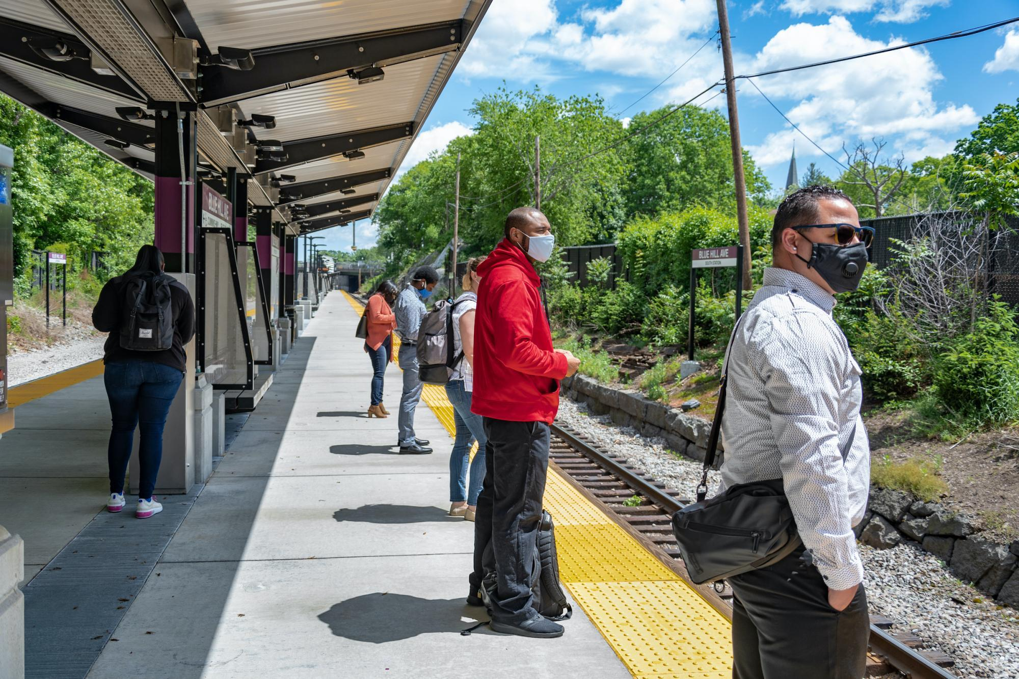 Customers at the Blue Hill Ave Commuter Rail platform, wearing face coverings