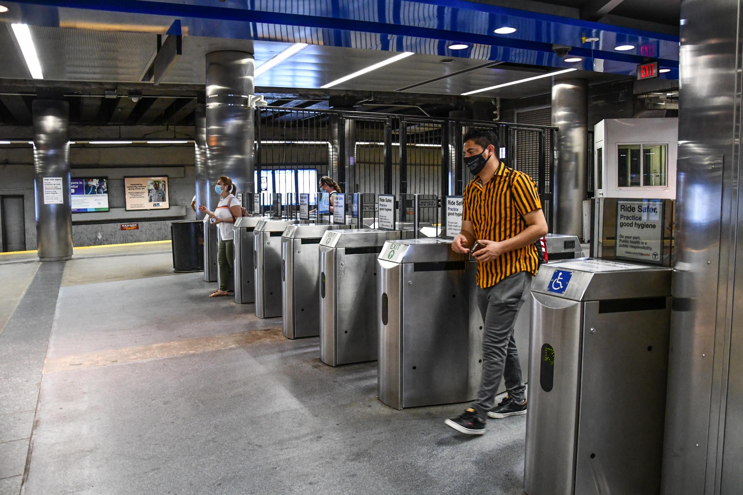A Blue Line rider wearing a face mask passes through fare gates at Maverick Station