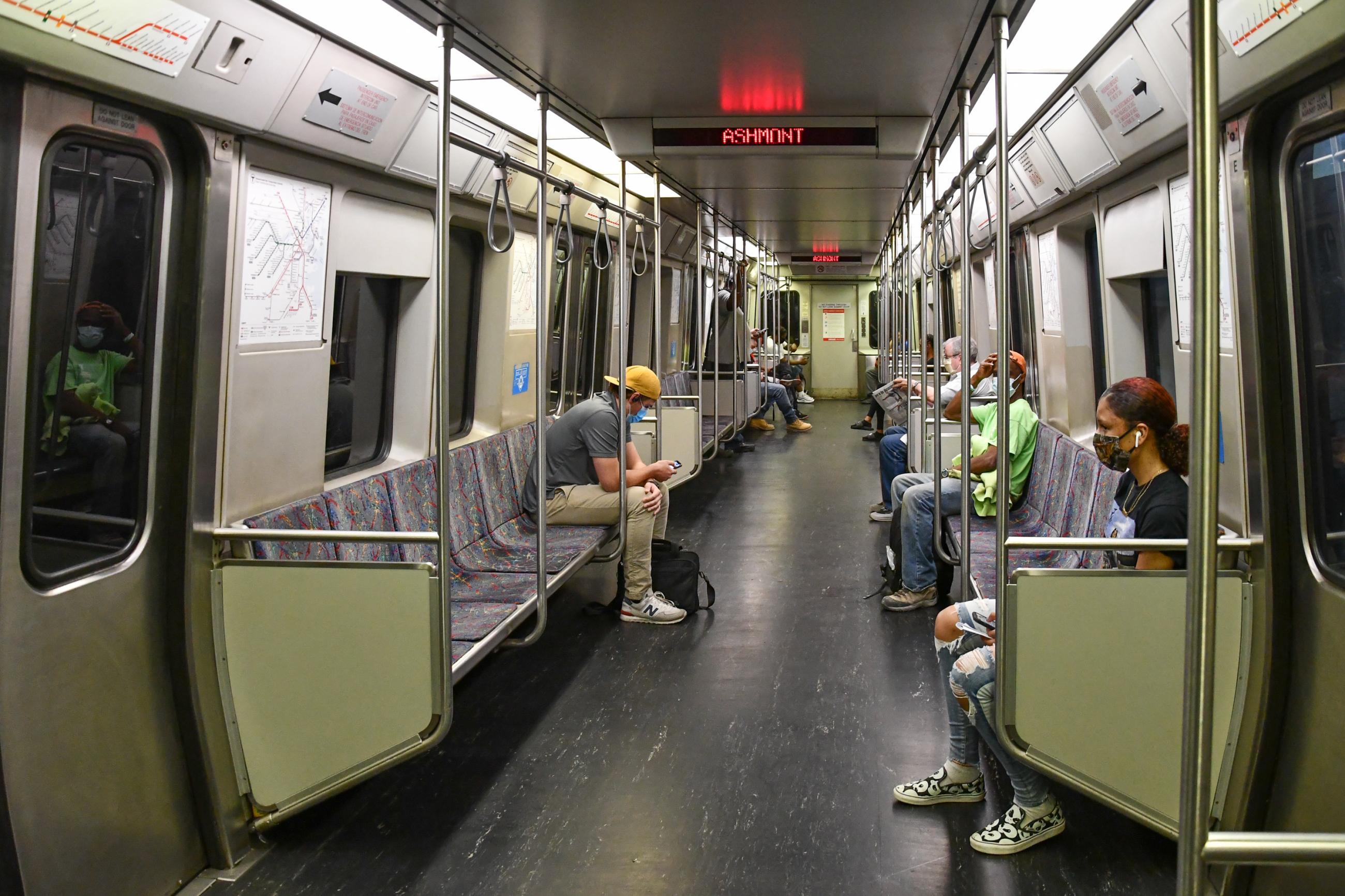 Red Line riders are seated far apart from each other, each wearing a face mask
