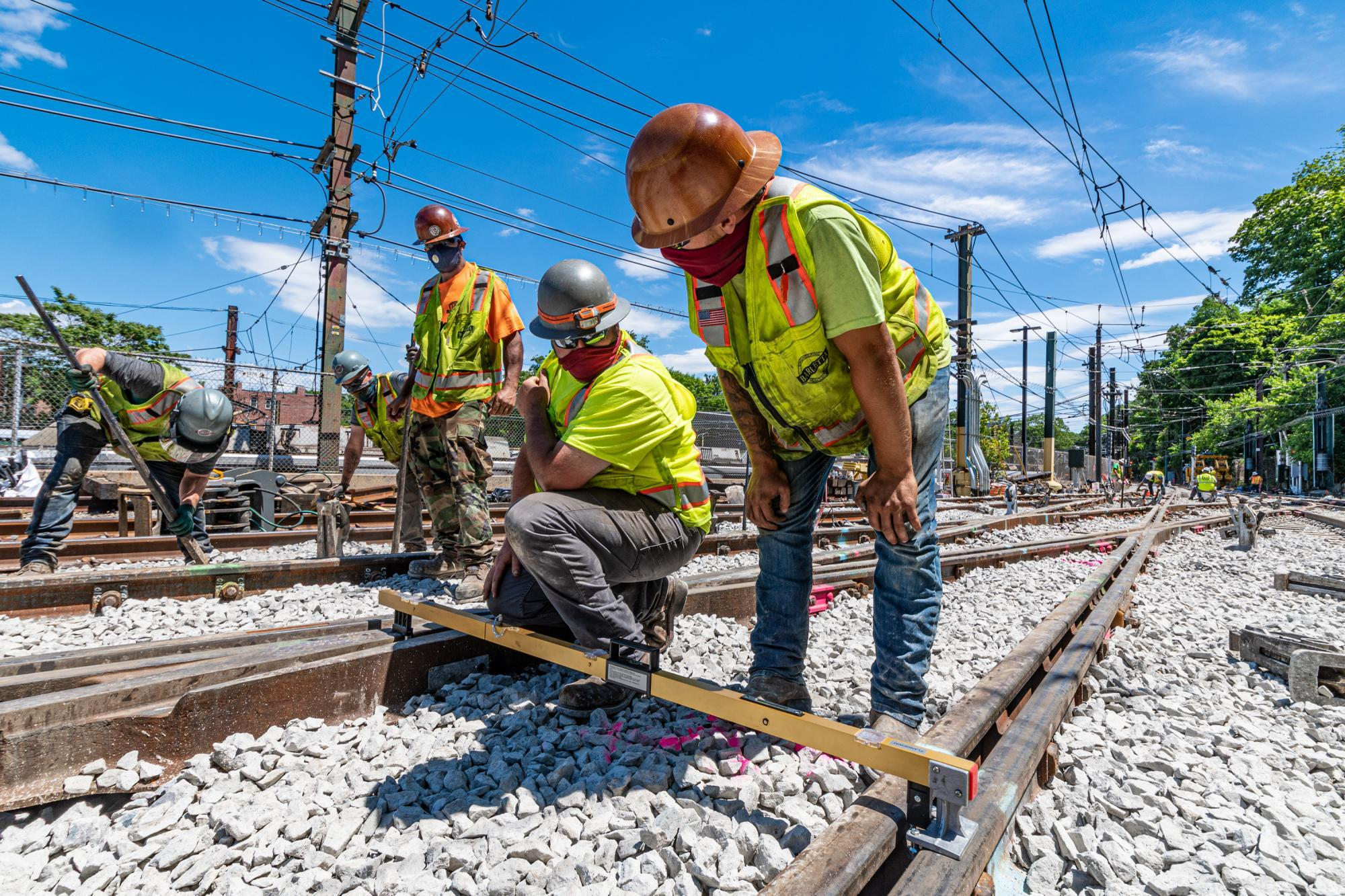 A crew aligns track and installs ballast near Reservoir Station on the Green Line D
