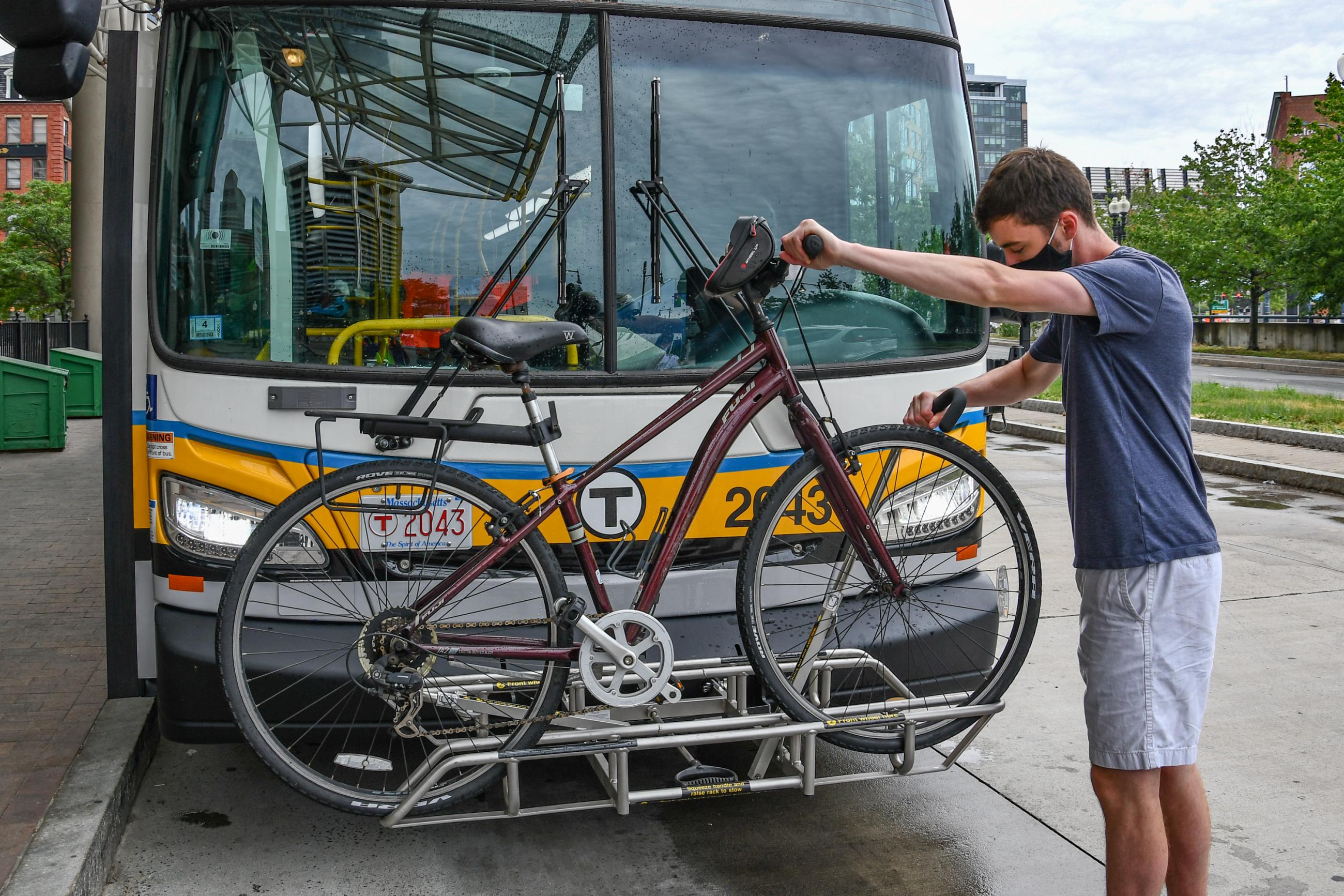 A person secures a bicycle on the bike rack on the front of a bus at Haymarket station