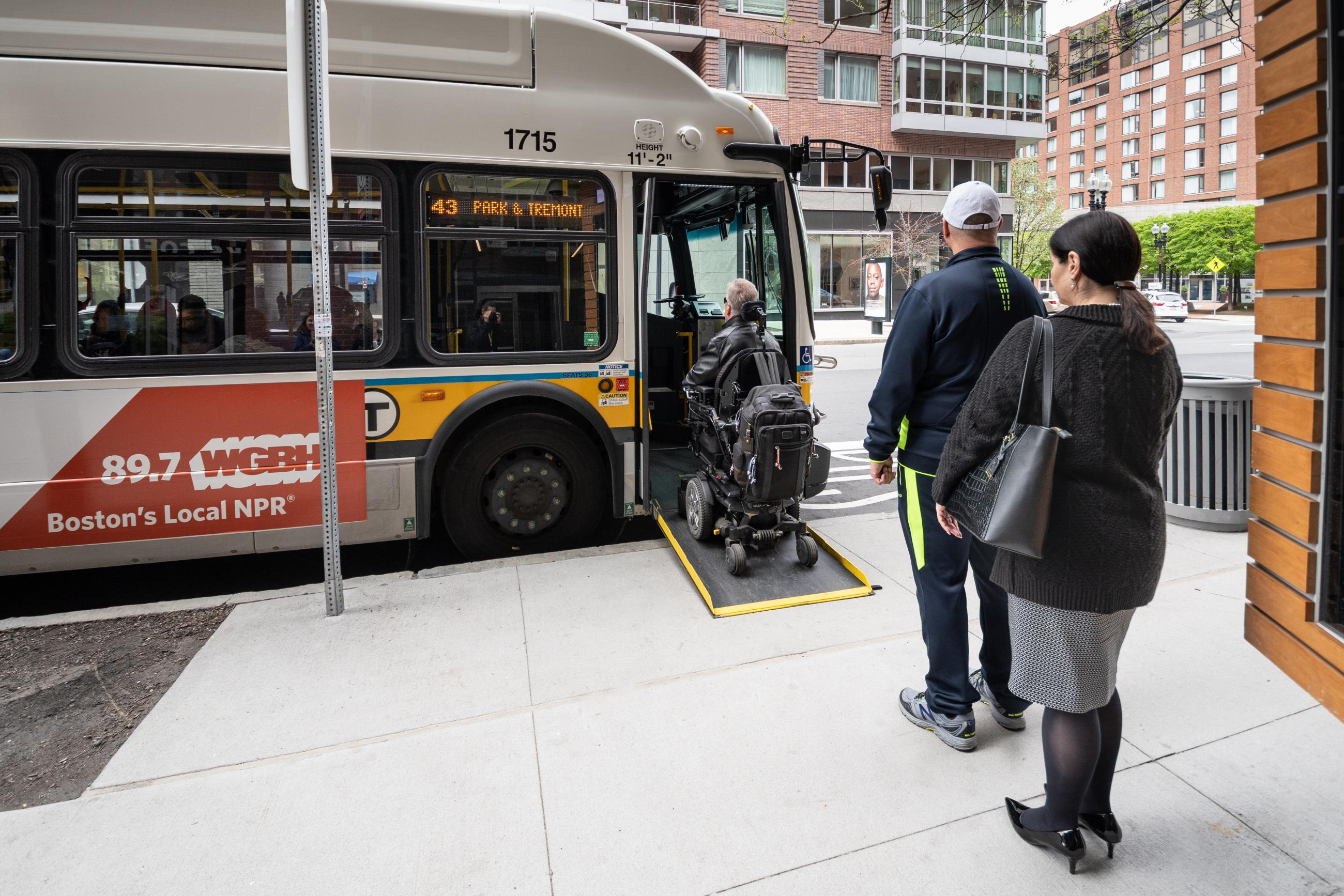 At a bus stop, a rider in a wheeleed mobility device boards the bus via a ramp, as two other riders wait in line behind.