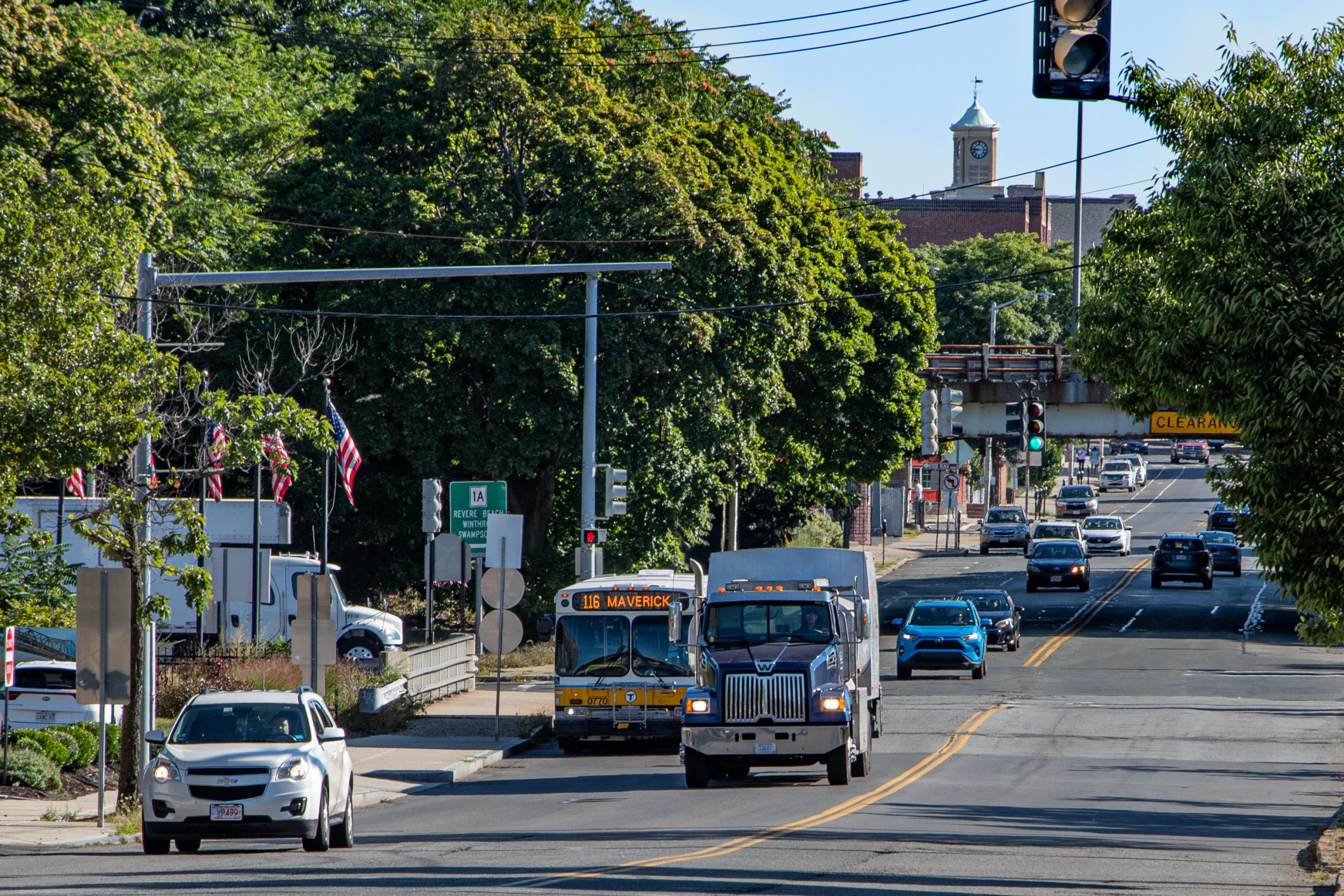View of Broadway Ave in Chelsea on a cloudless summer day. The 116 bus is in light traffic.