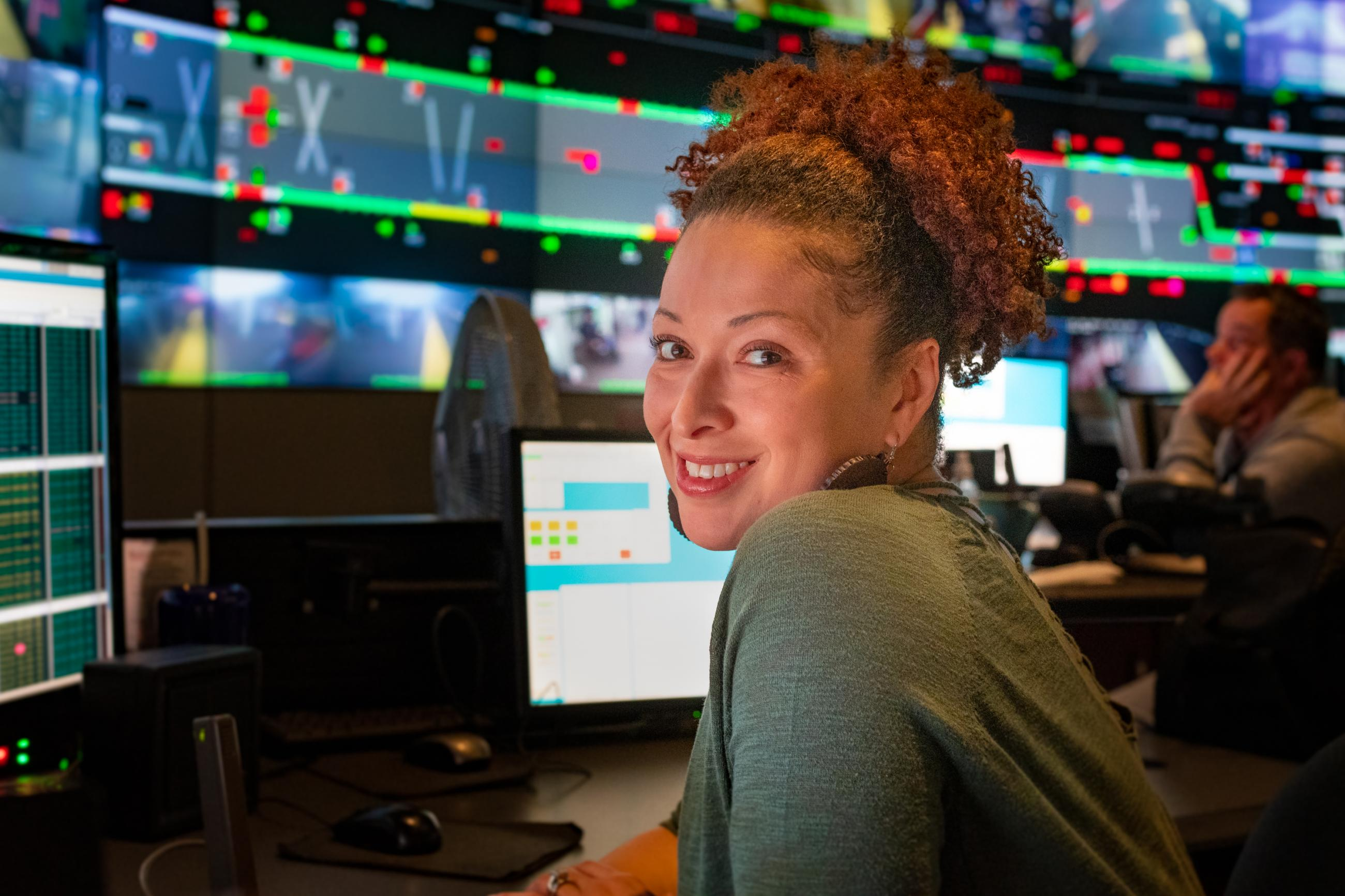 An employee at the Operations Control Center, with computer screens behind her
