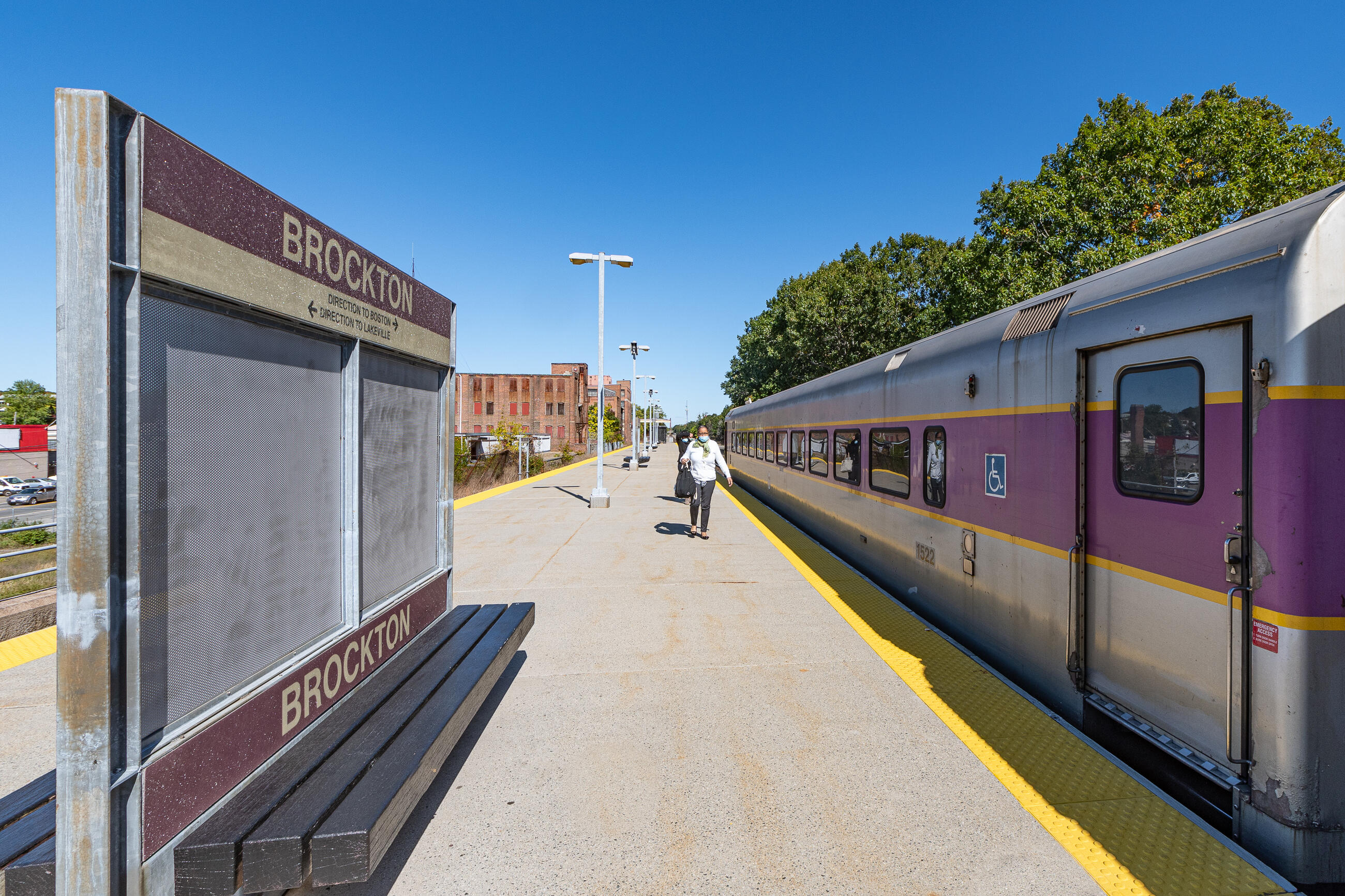 Commuter Rail platform at Brockton Statoin, with a train pulled up, and a masked rider walking.