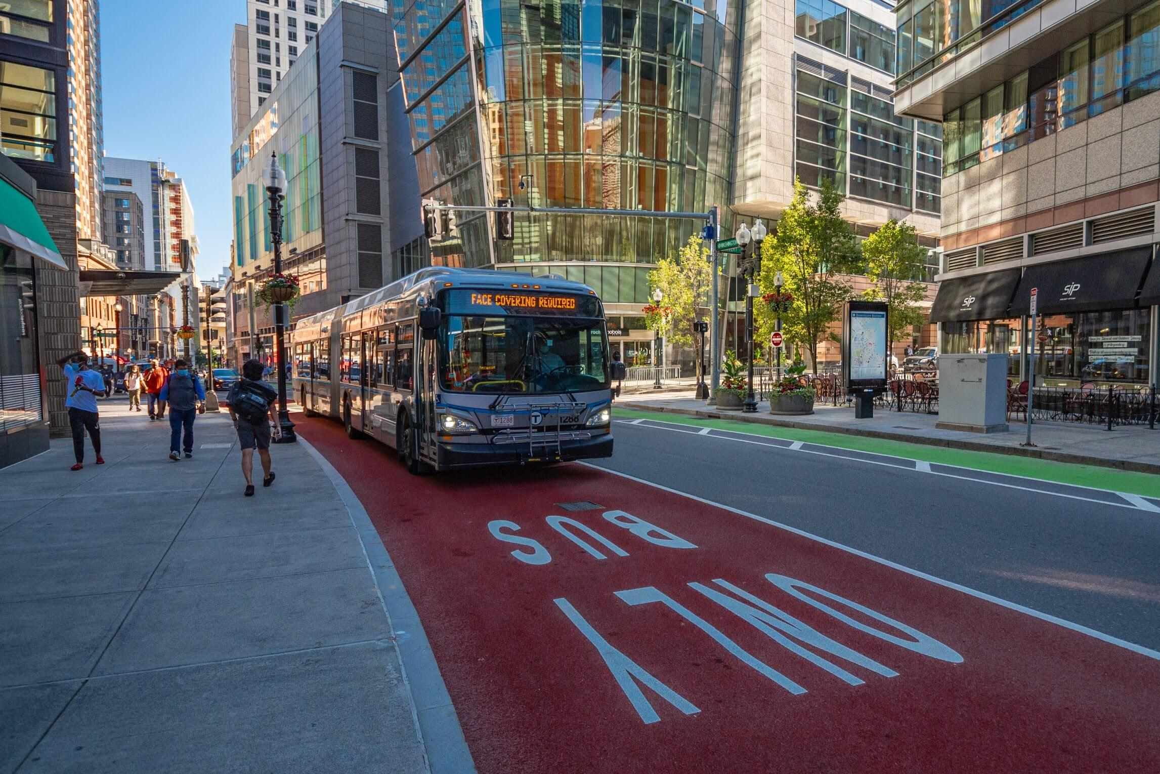 """Silver Line bus in a bus lane along Washington St in Downton Boston, with a headsdign that reads """"Face Masks Required"""""""