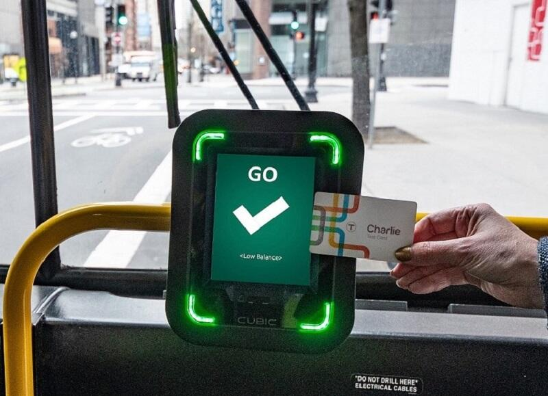 A rider taps the new Charlie Card at one of the CharlieCard reader prototypes installed on bus routes 28 and 39
