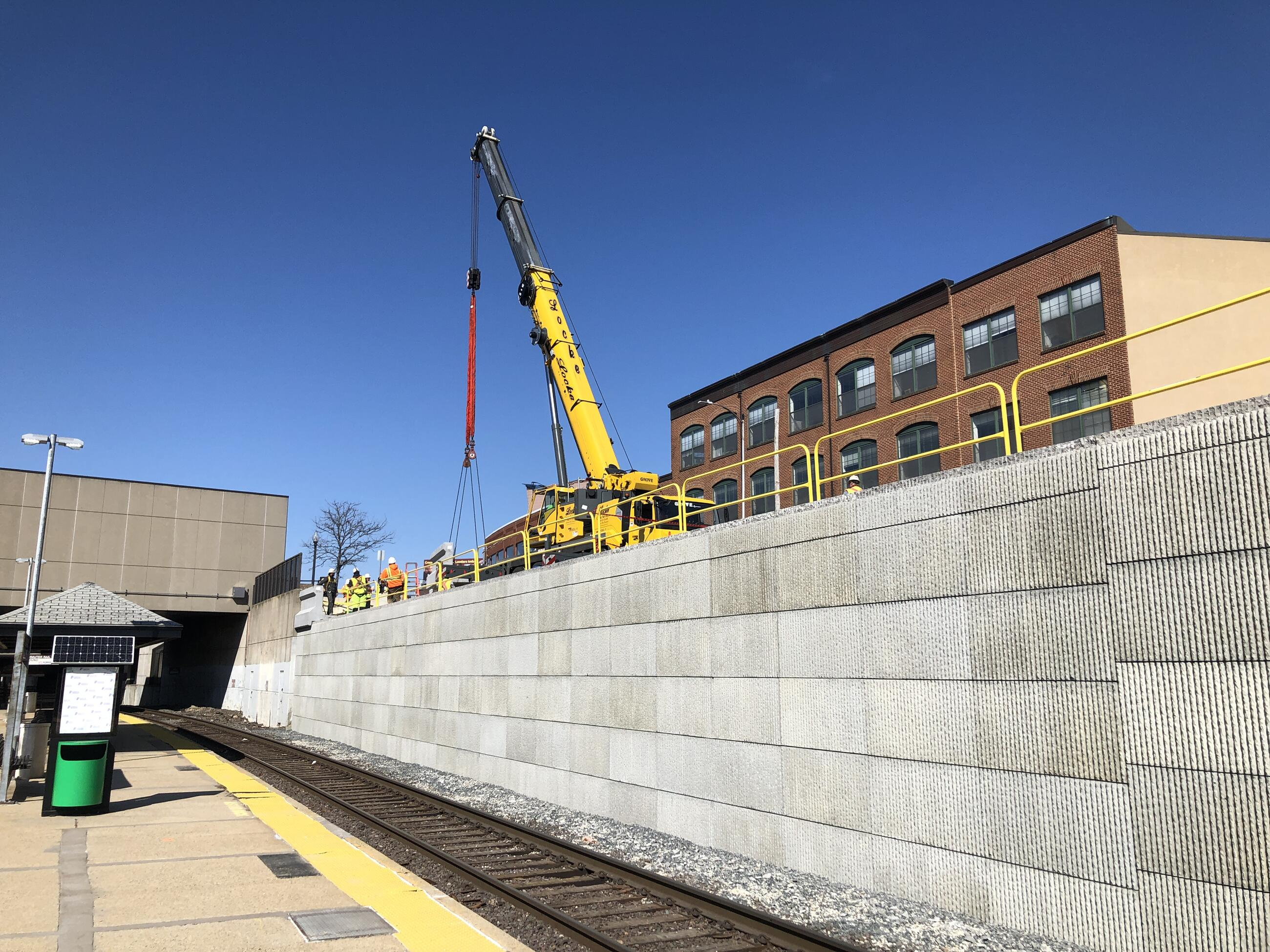 A new concrete retaining wall next to the tracks at Porter Station. Construction workers and equipment are visible on top on the wall.