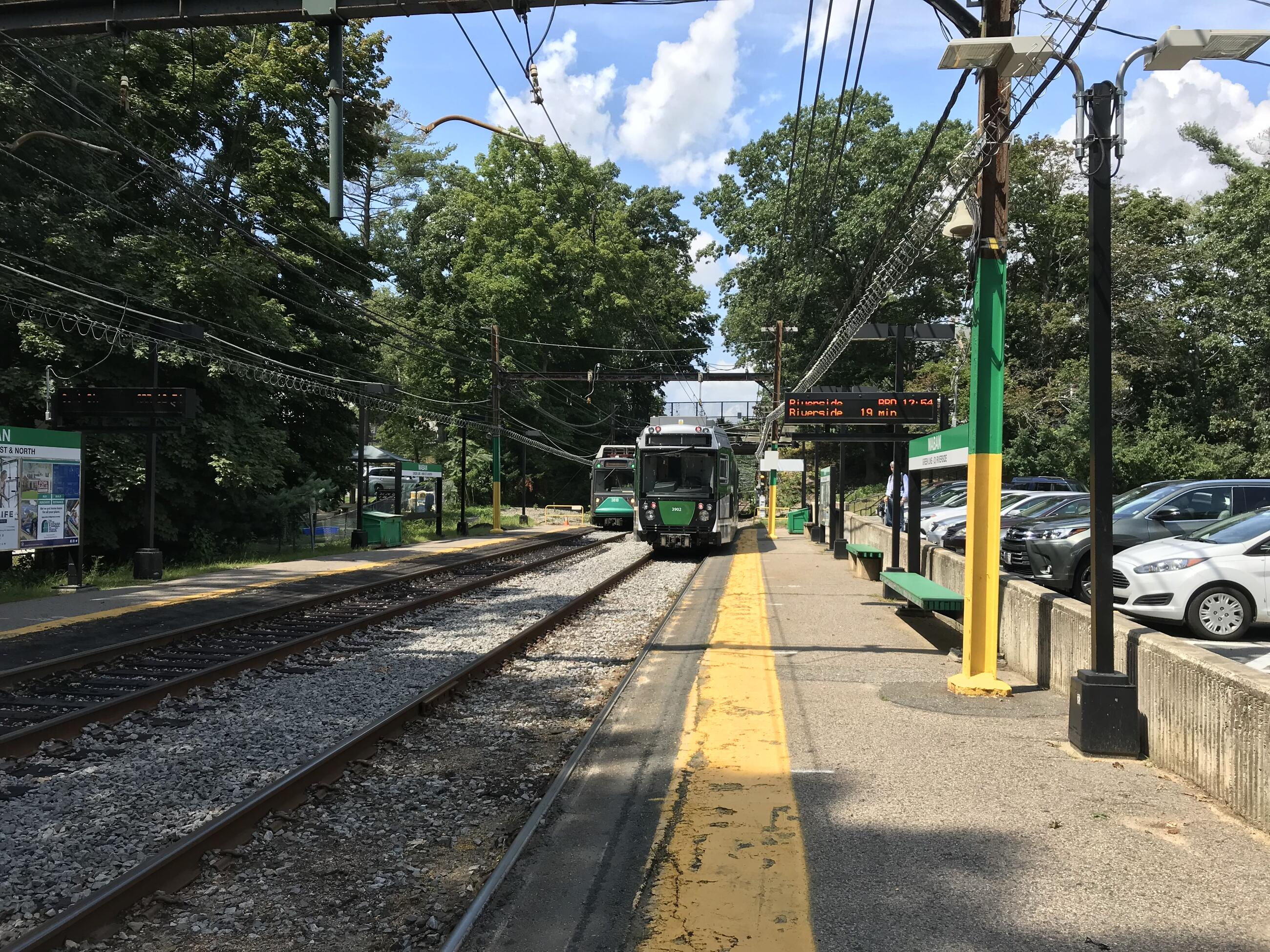 A Green Line train at the Waban station. The entire platform and tracks are visible
