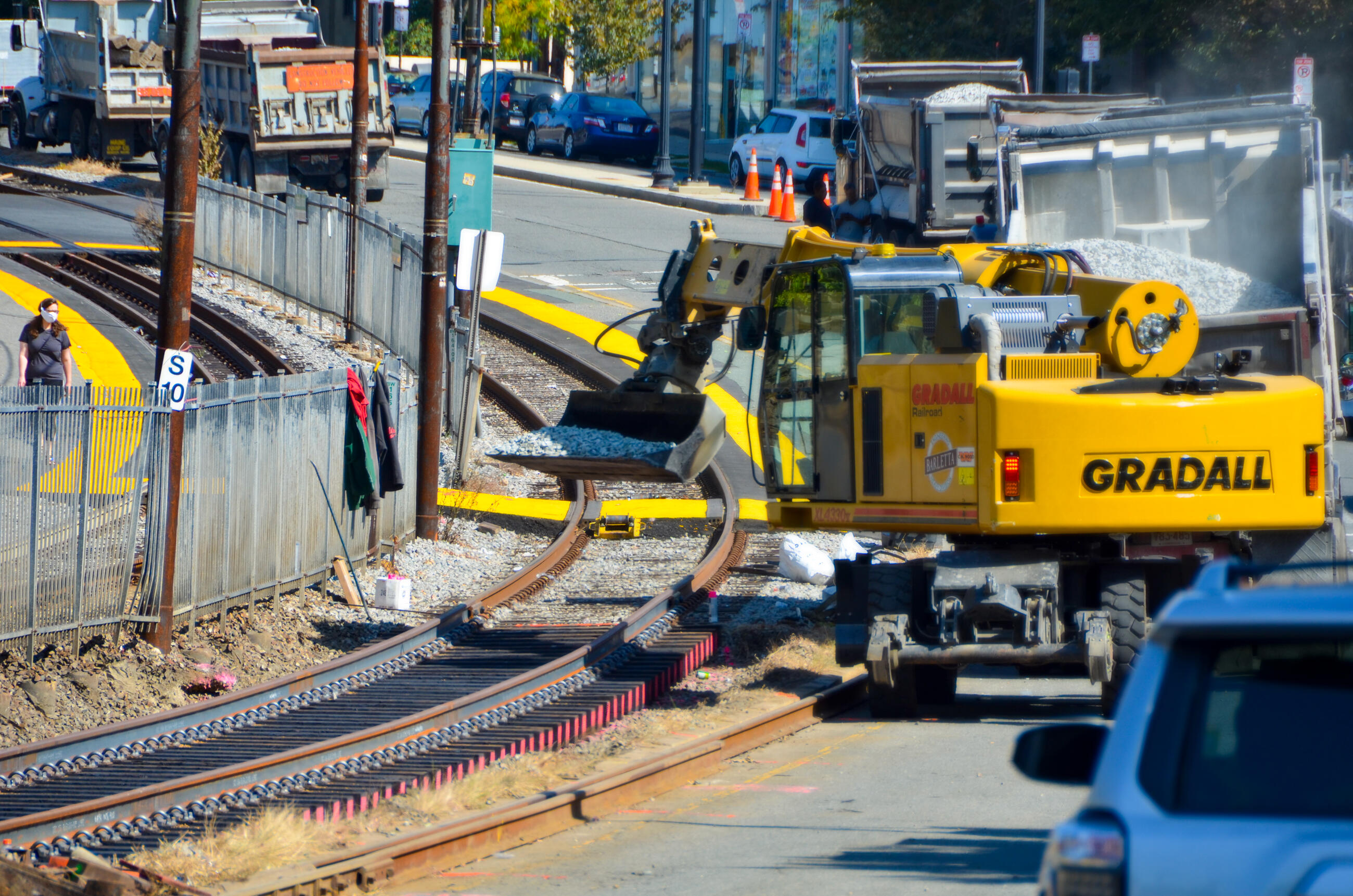 A large construction vehicle moves gravel onto freshly laid track. The track curves around a fence next to a street.