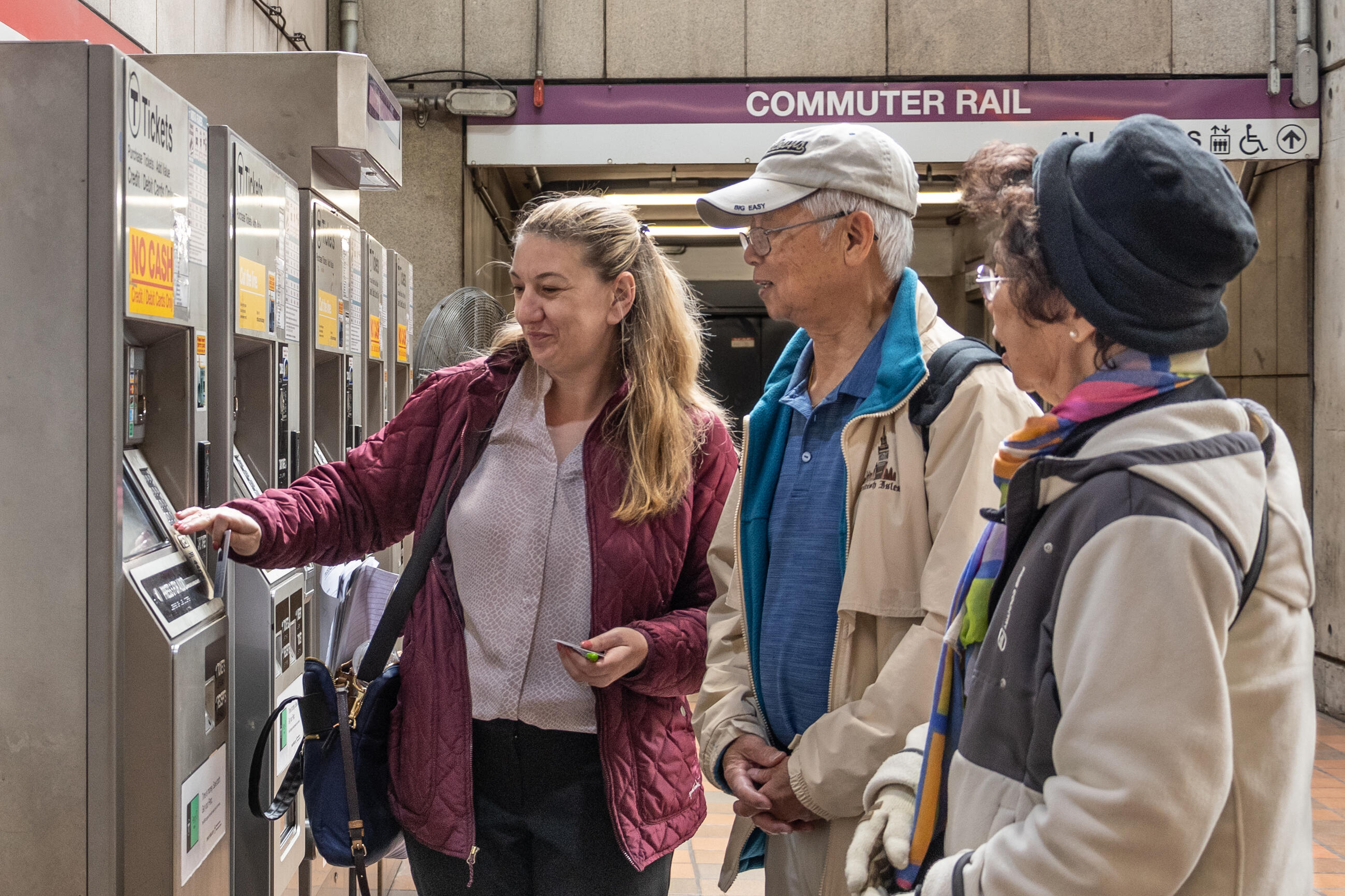 A woman helps two elderly riders purchase tickets at a commuter rail station