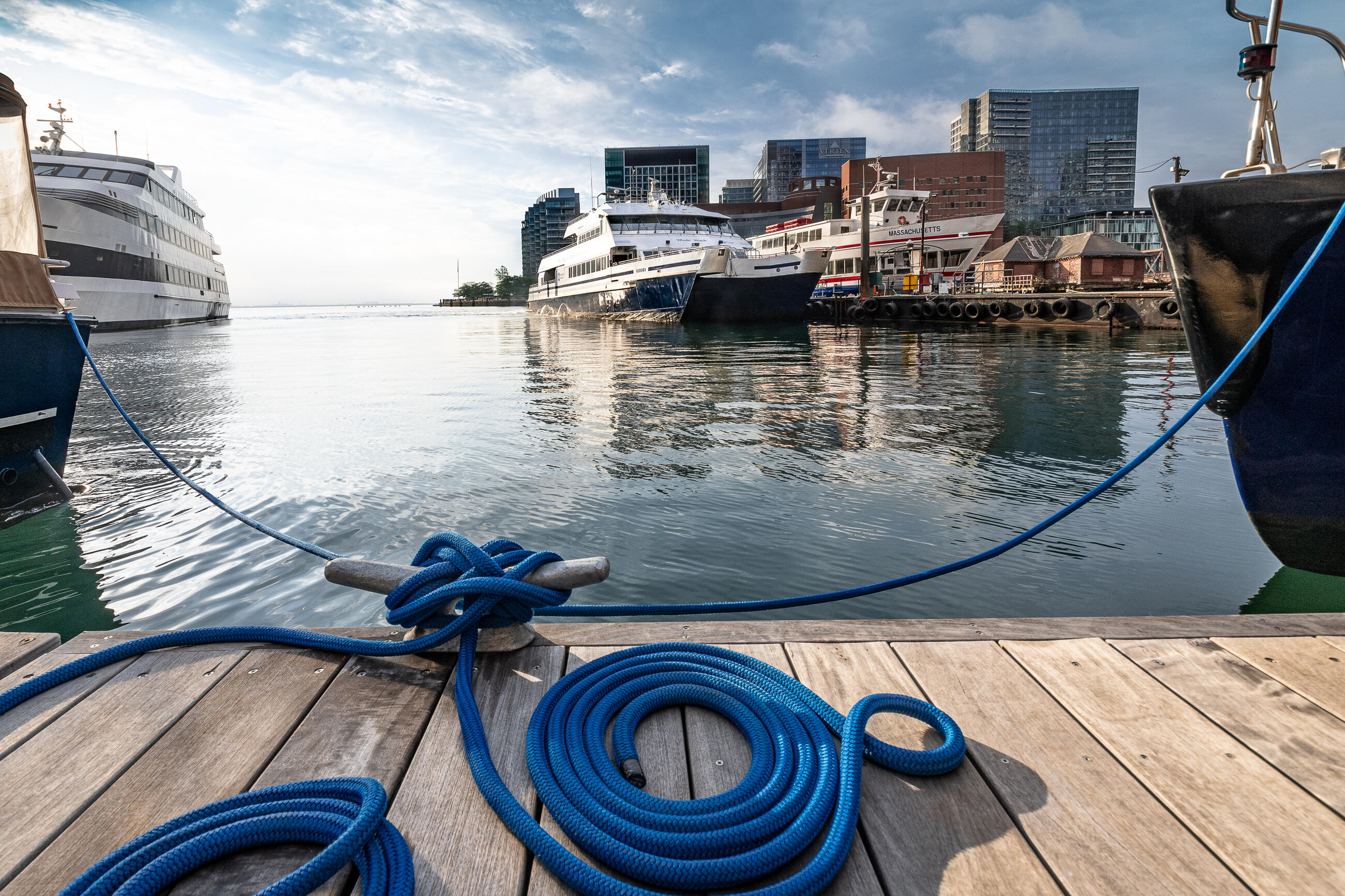 A photo of a ferry in the water, taken from the Rowes Wharf dock. There's a large blue rope tied to the dock in the foreground.