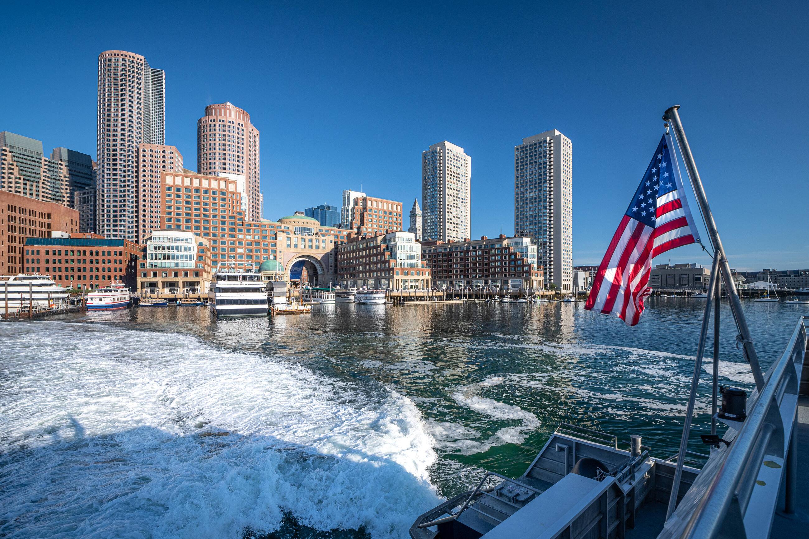 A photo of Rowes Wharf, taken from the ferry across the water. The water is white from the wake of the ferry moving in the water. A United States flag is flying at an angle from the side of the boat, and the sky is a bright clear blue