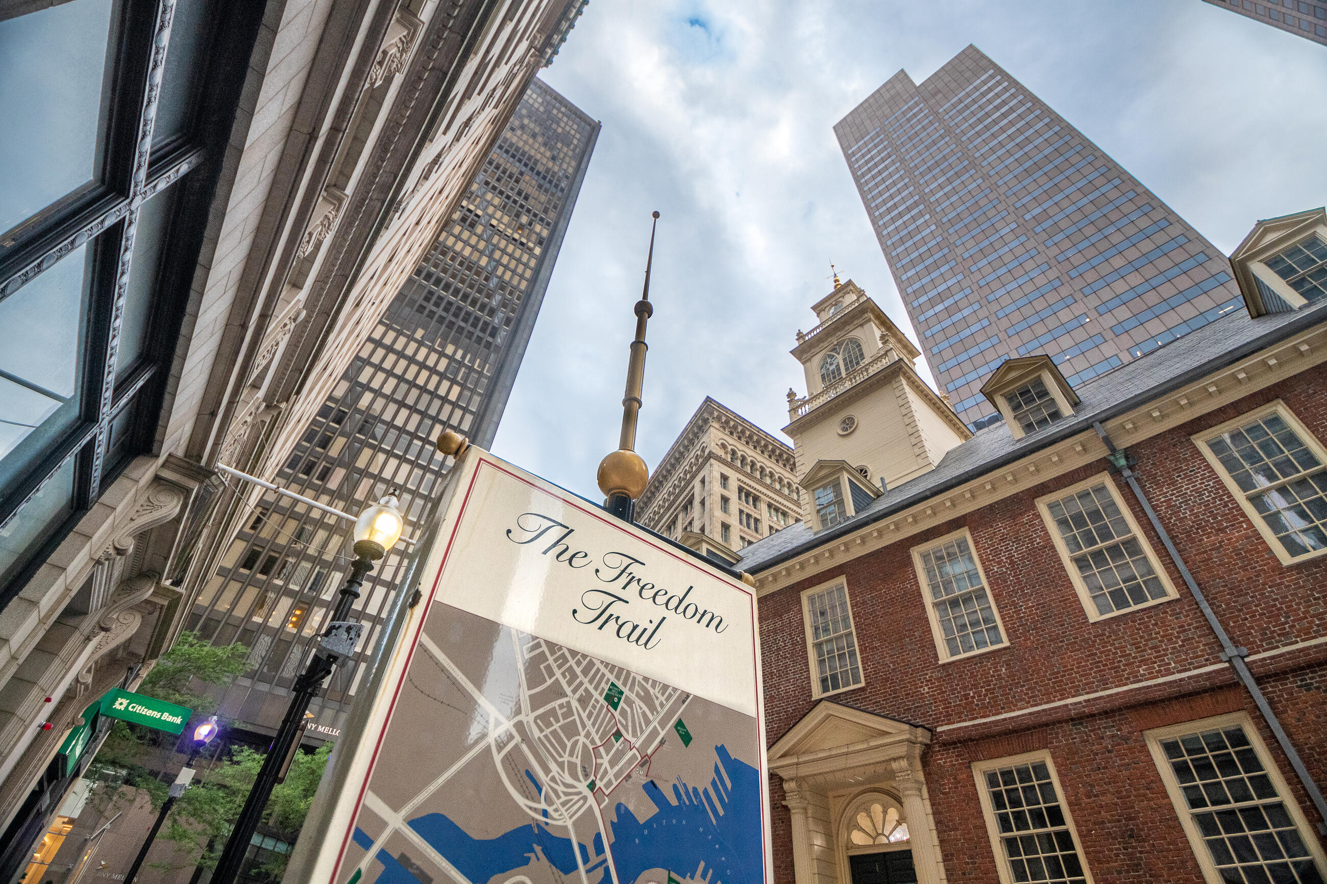 A large standing sign with a map of the Freedom Trail. The Old State House is in the background