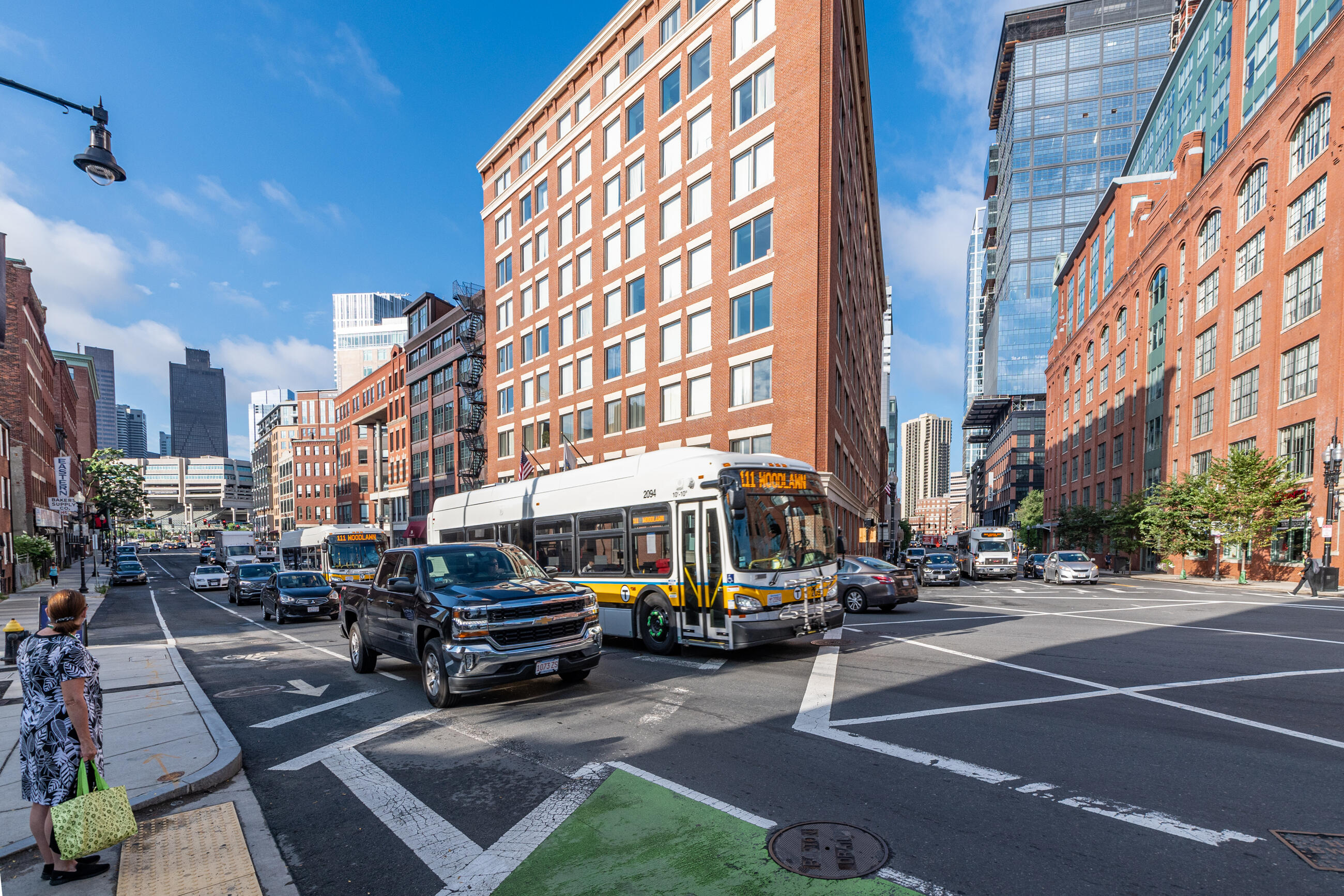 Two Route 111 buses travel along a congested stretch of North Washington Street near Causeway Street in Boston before construction of a northbound bus lane.