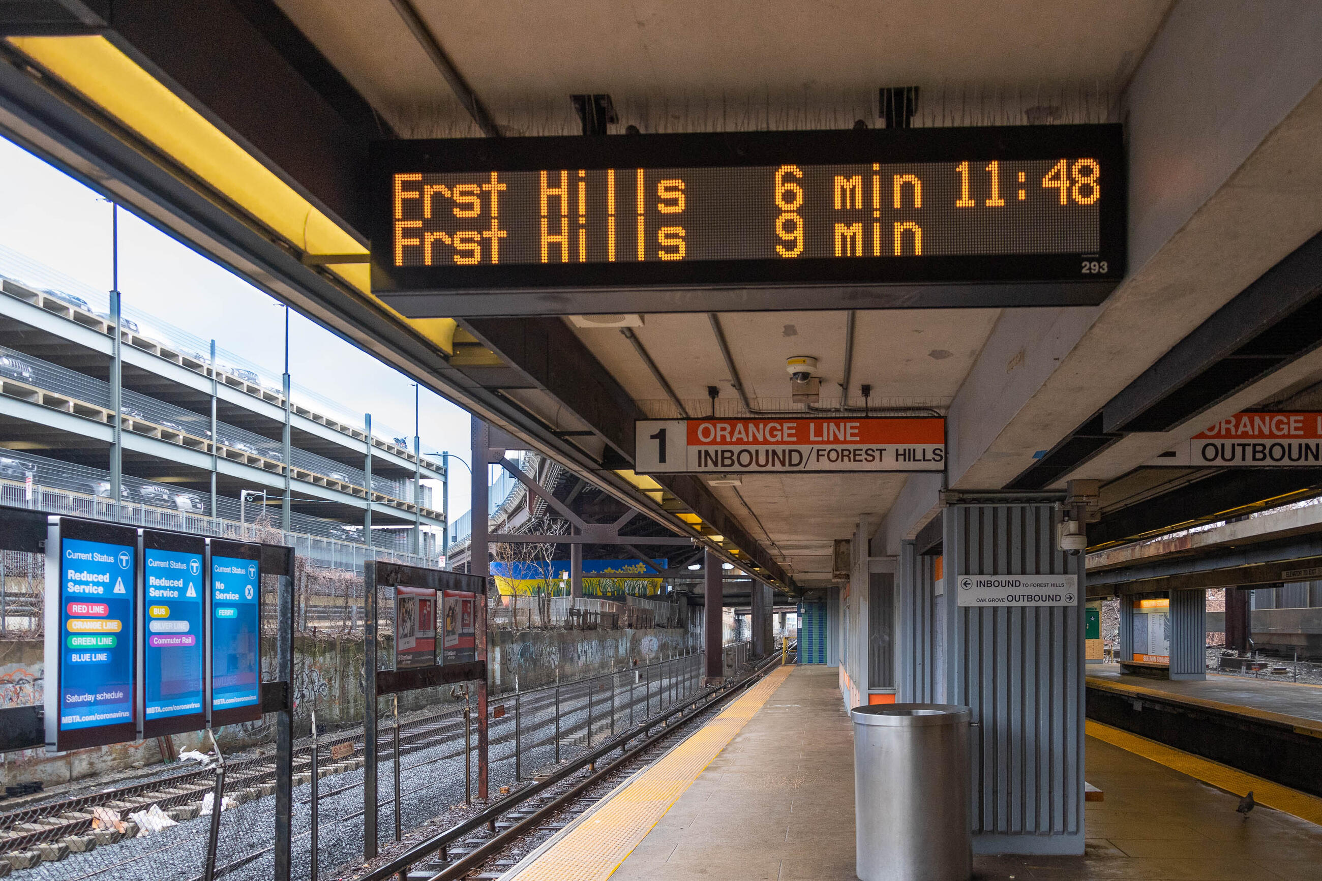 """A photo of a countdown clock at Forest Hills station on the Orange Line. It says """"Frst Hills 6 min 11:48, Frst Hills 9 min"""". The tracks and some screens showing reduced service information are to the left of the platform"""