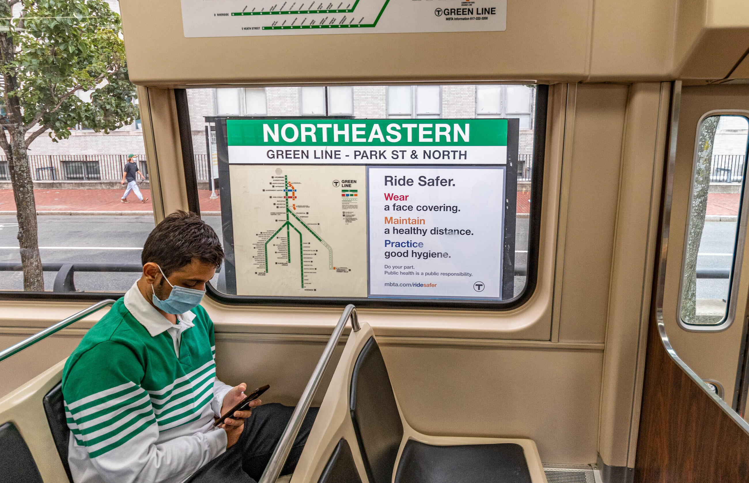 Person on the green line, with a Ride Safer sign in the background