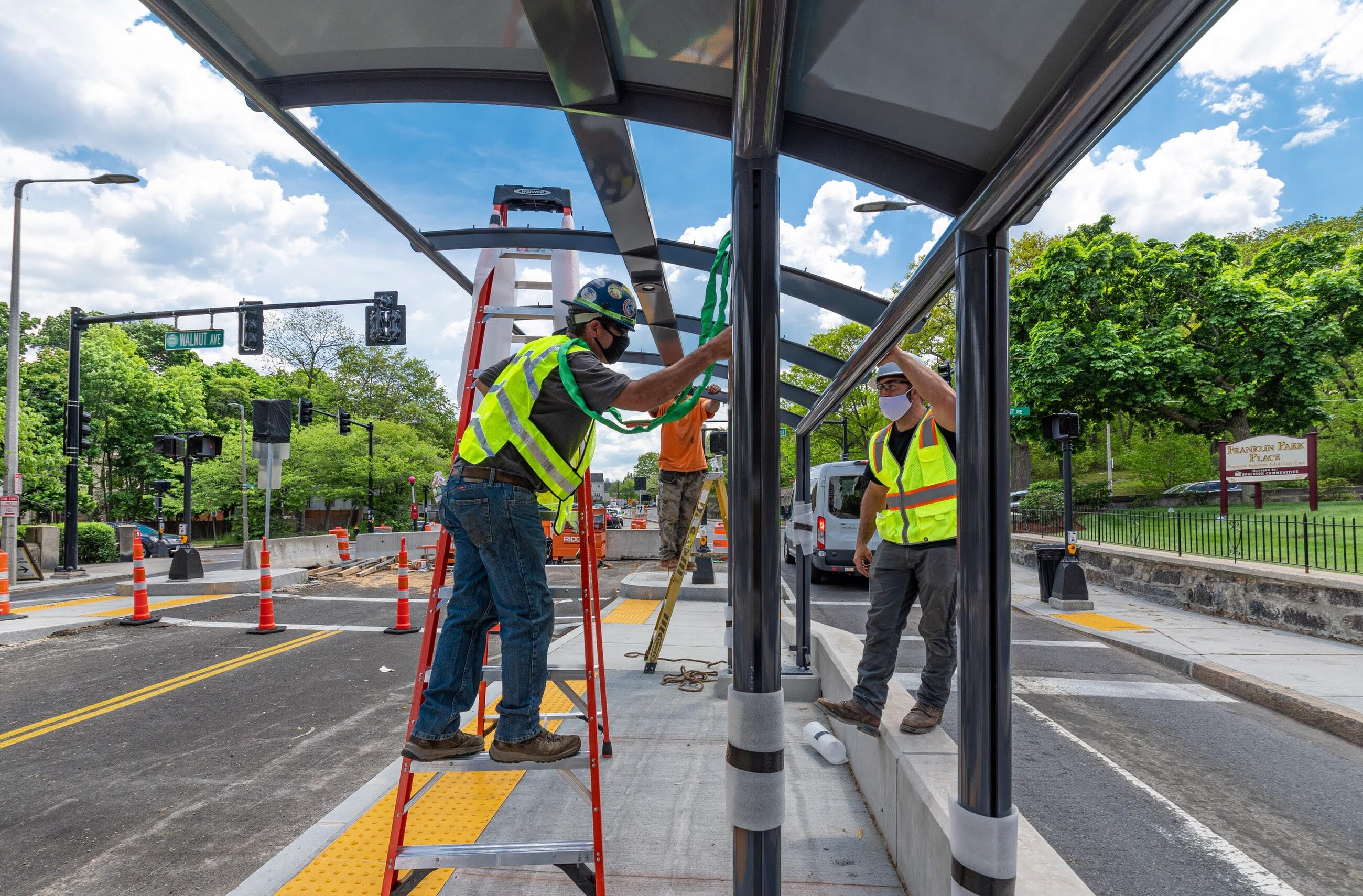 Construction workers in high visibility clothing and hard hats work together to assemble a glass and metal canopy for shelter at the new bus stop