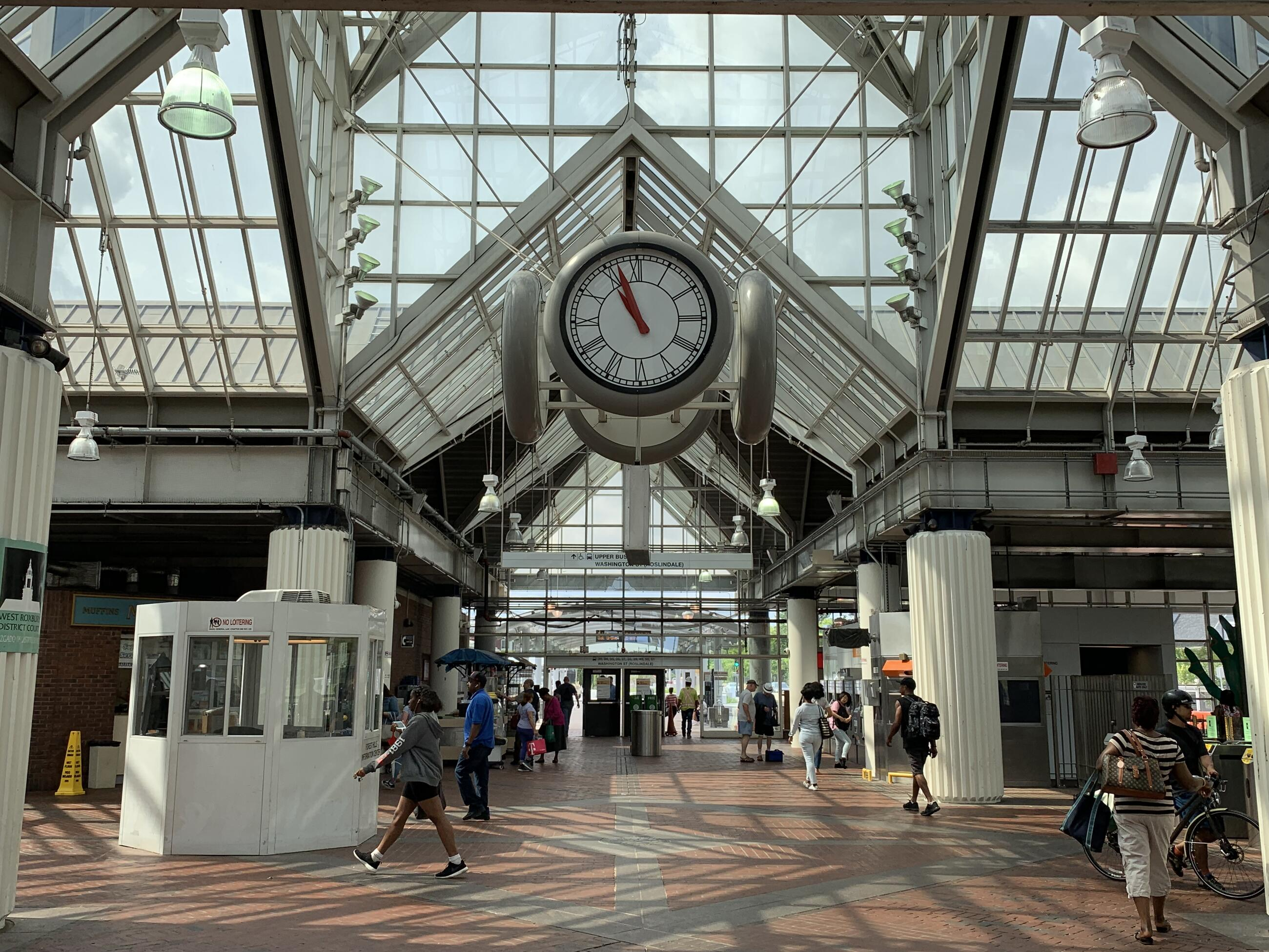 A photo of the interior of Forest Hills station, showing the clock and facing towards the upper busway. Many people are walking through the station.
