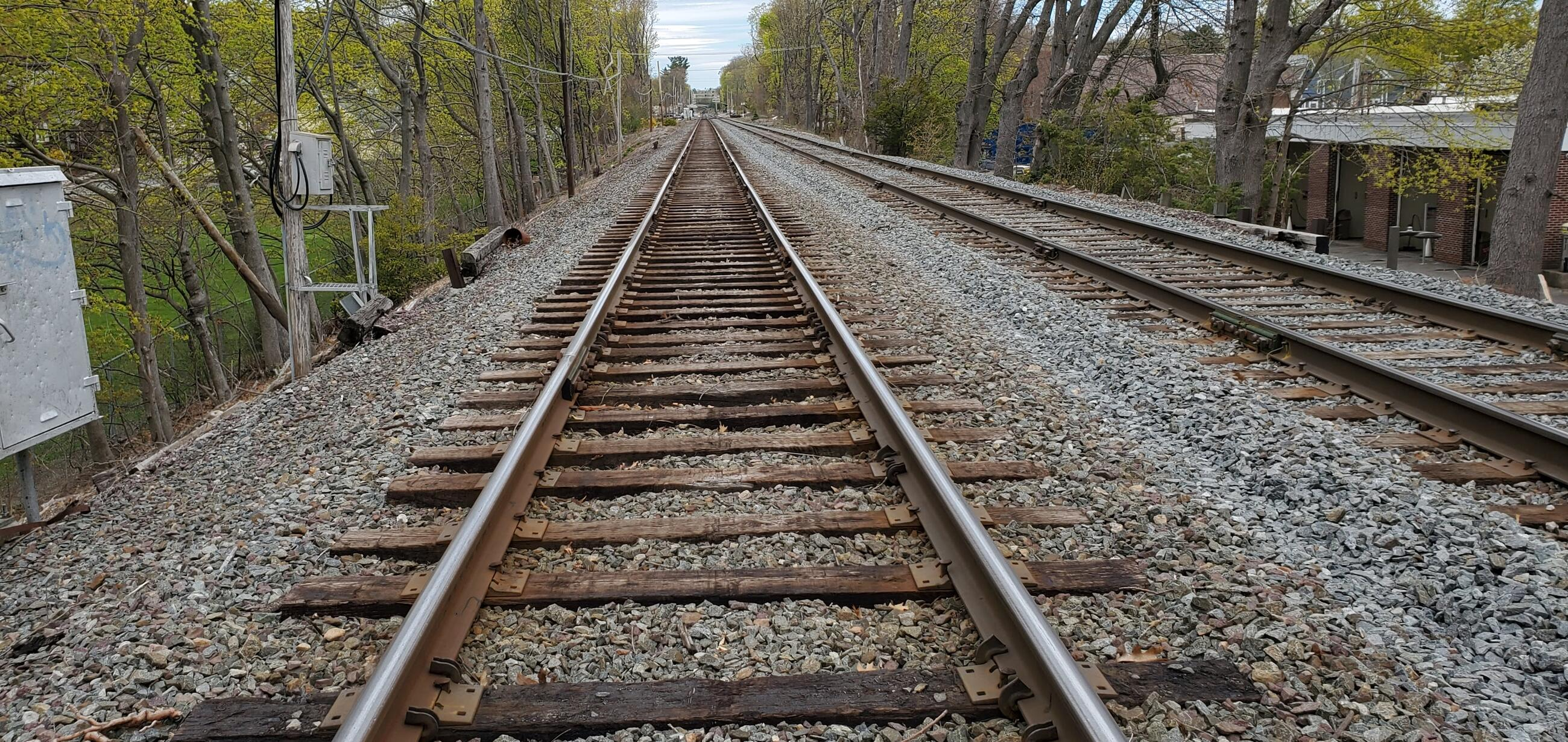 A length of empty Commuter Rail rail and tracks is shown from a vantage point next to the center of the tracks, between the rails, with the track disappearing into the distance at the top. Another empty track is to the right. The two tracks are flanked by gravel and trees, with grass at the left and a building at the right.