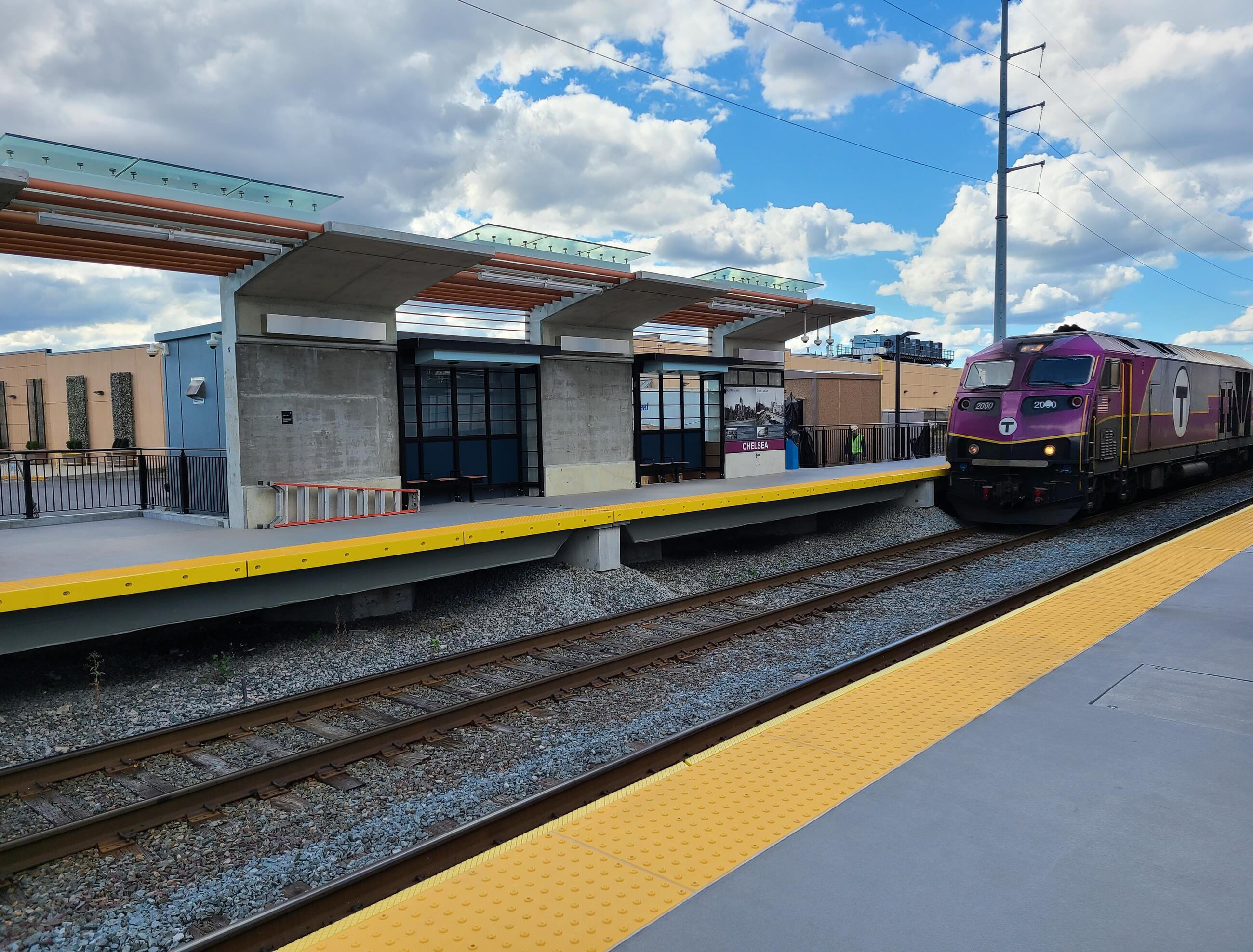 A purple Commuter Rail train is shown at right next to the new station platform. The track runs diagonally from lower left to center right, with the inbound platform at lower right and the outbound platform at upper left. The platform has lighted canopies hanging over outdoor stools in recessed seating areas. A blue sky with white clouds is overhead at upper right.