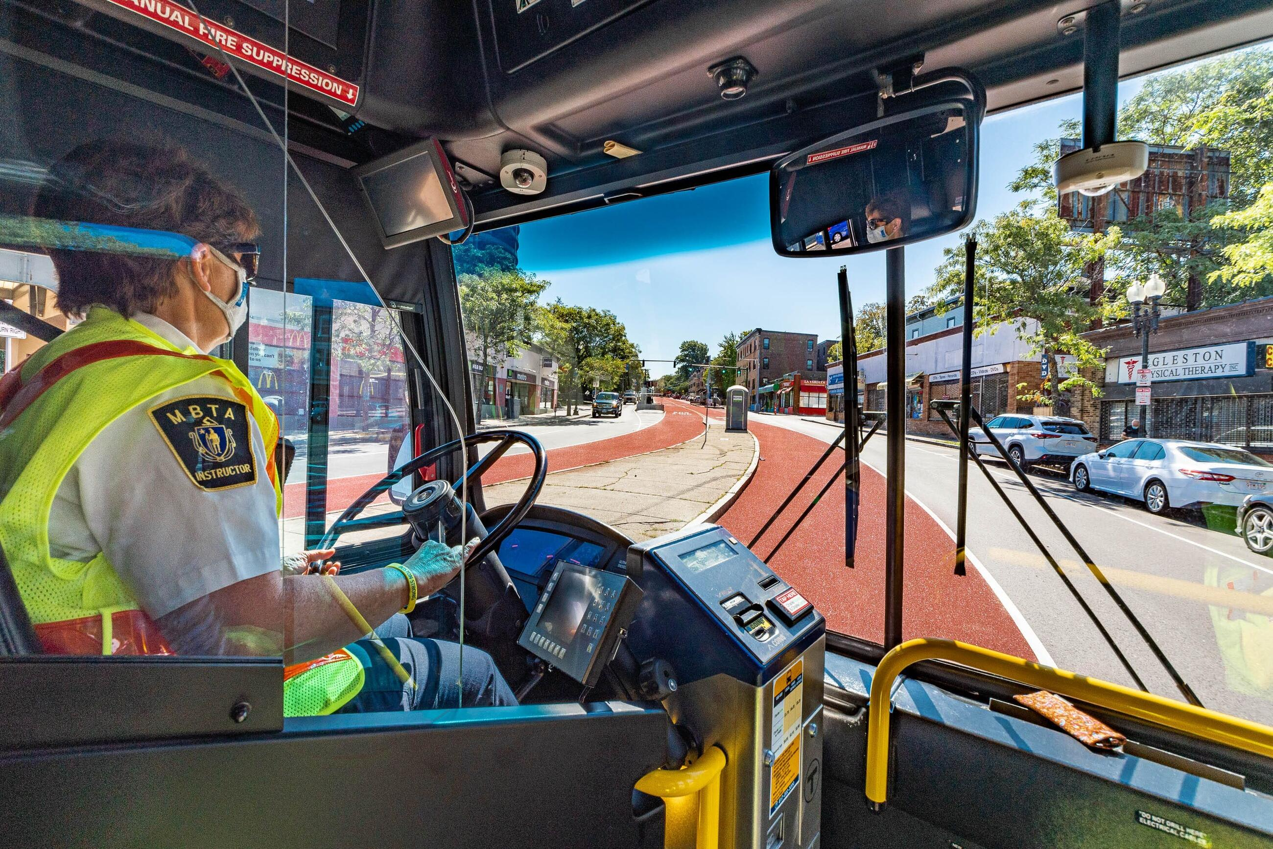 """Photo taken from inside a bus of a masked driver with an """"MBTA instructor"""" shirt patch driving down the columbus ave center lane"""