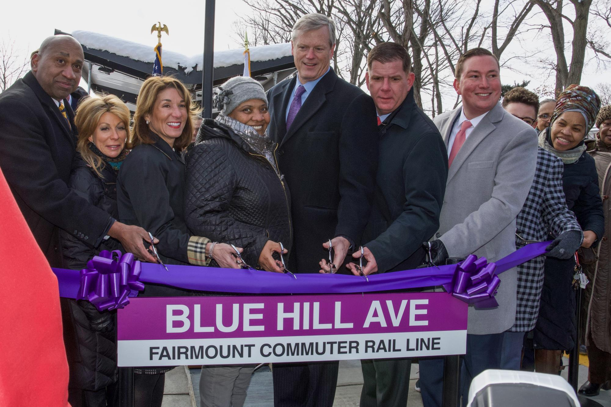 A group of elected officials and community members cut a purple ribbon to celebrate the opening of the Blue Hill Ave station.