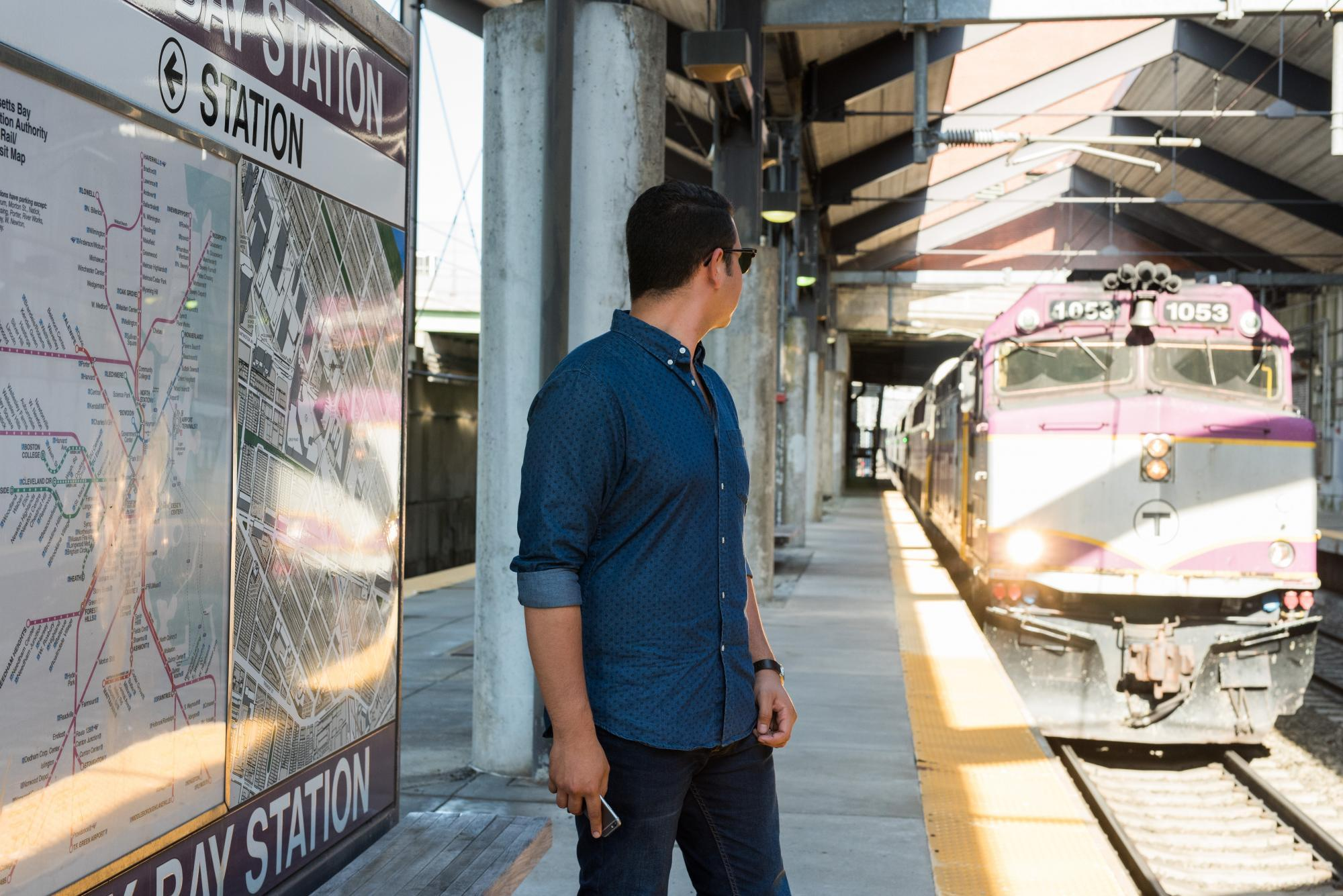 A man stands on the platform at Back Bay as a Commuter Rail train pulls in, awash in sunshine.