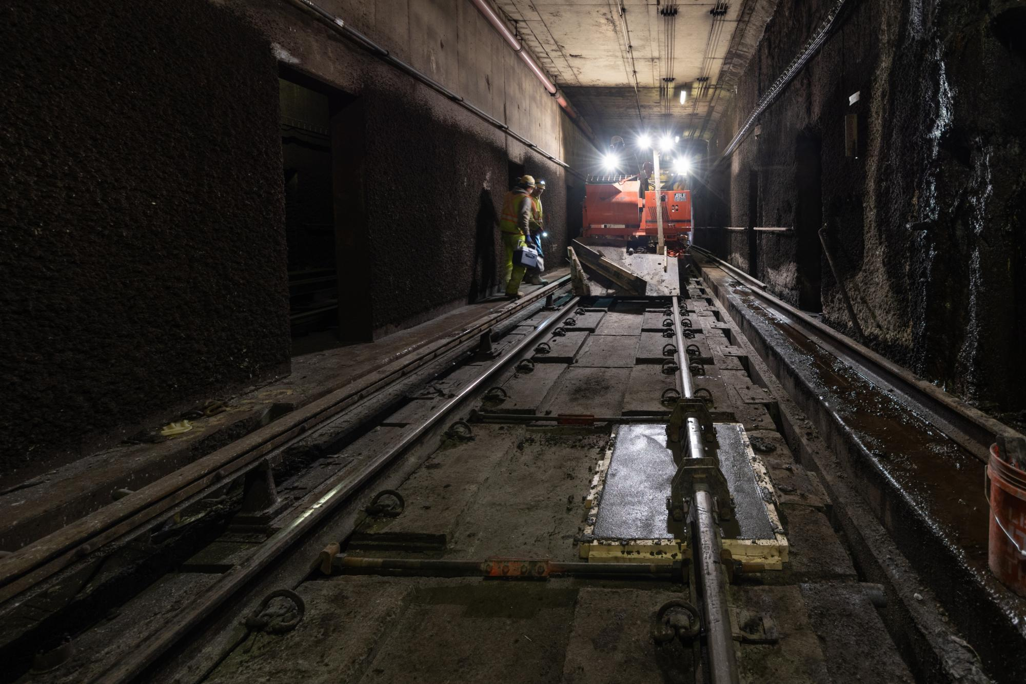 A crew works on maintenance in a tunnel