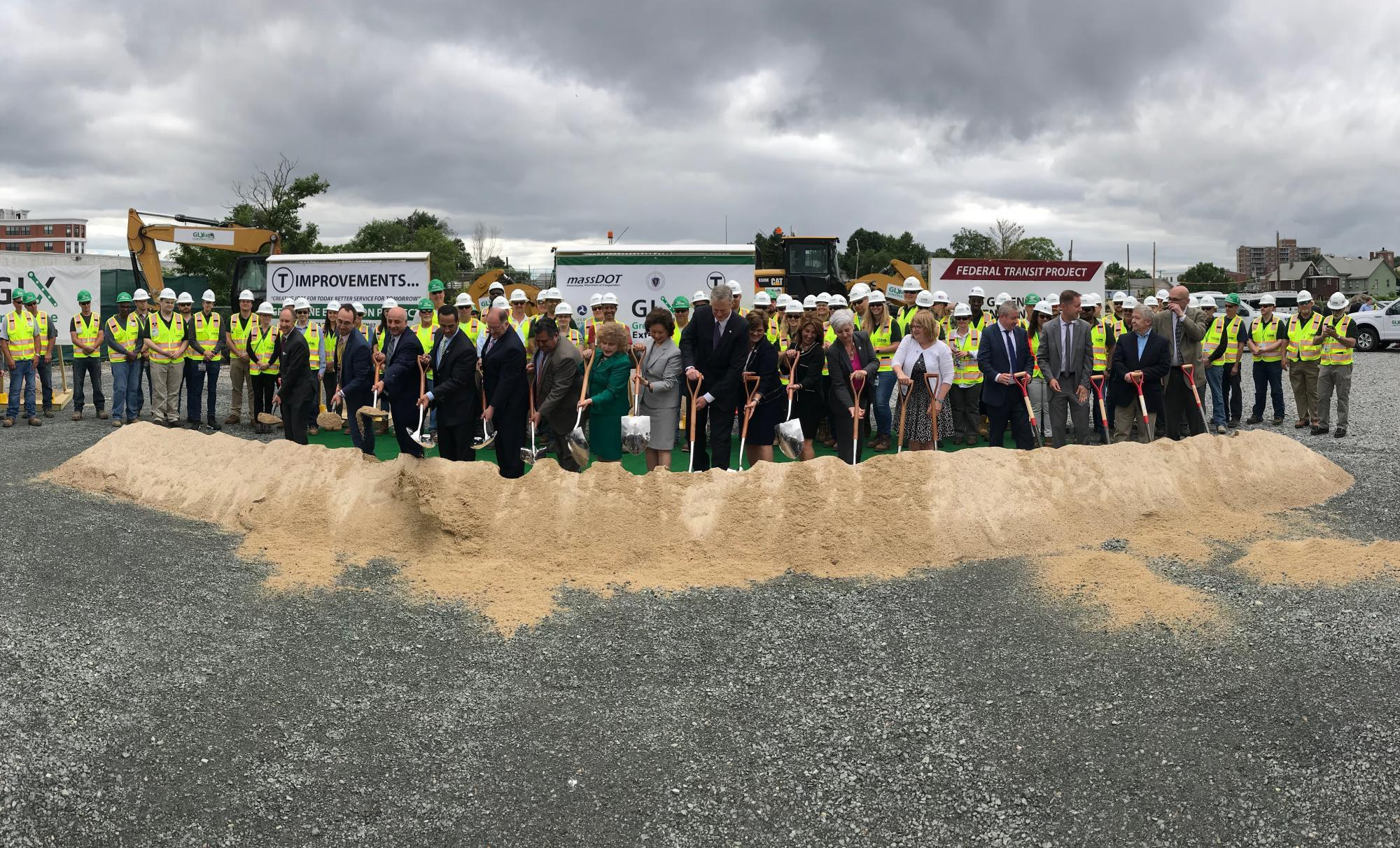 State officials pose with shovels at the Green Line Extension's groundbreaking ceremeony, with construction workings lined up as well