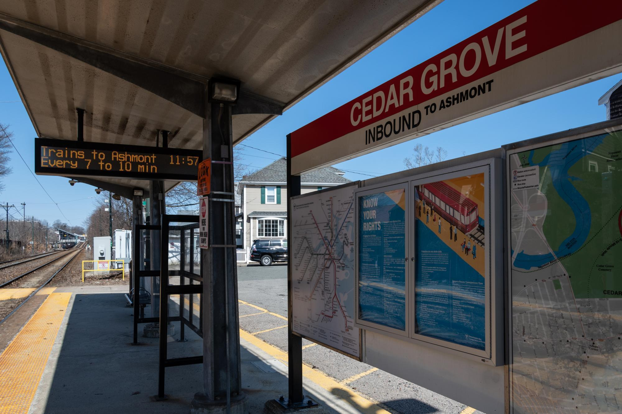 The station sign, maps, and coundown clock on the platform of Cedar Grove Station on the Mattapan Line