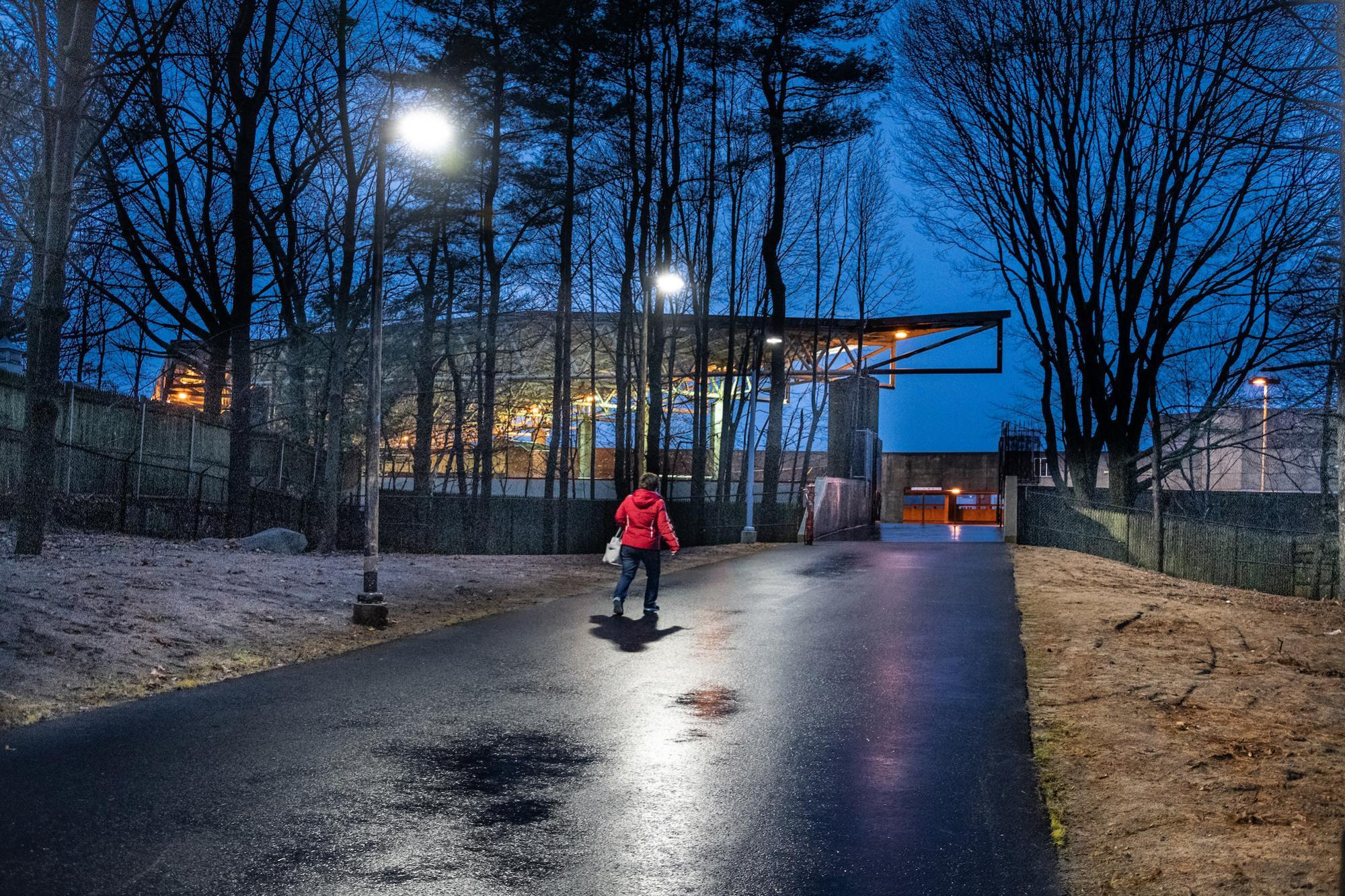 A woman walks on the paved path to the Quincy Adams gate