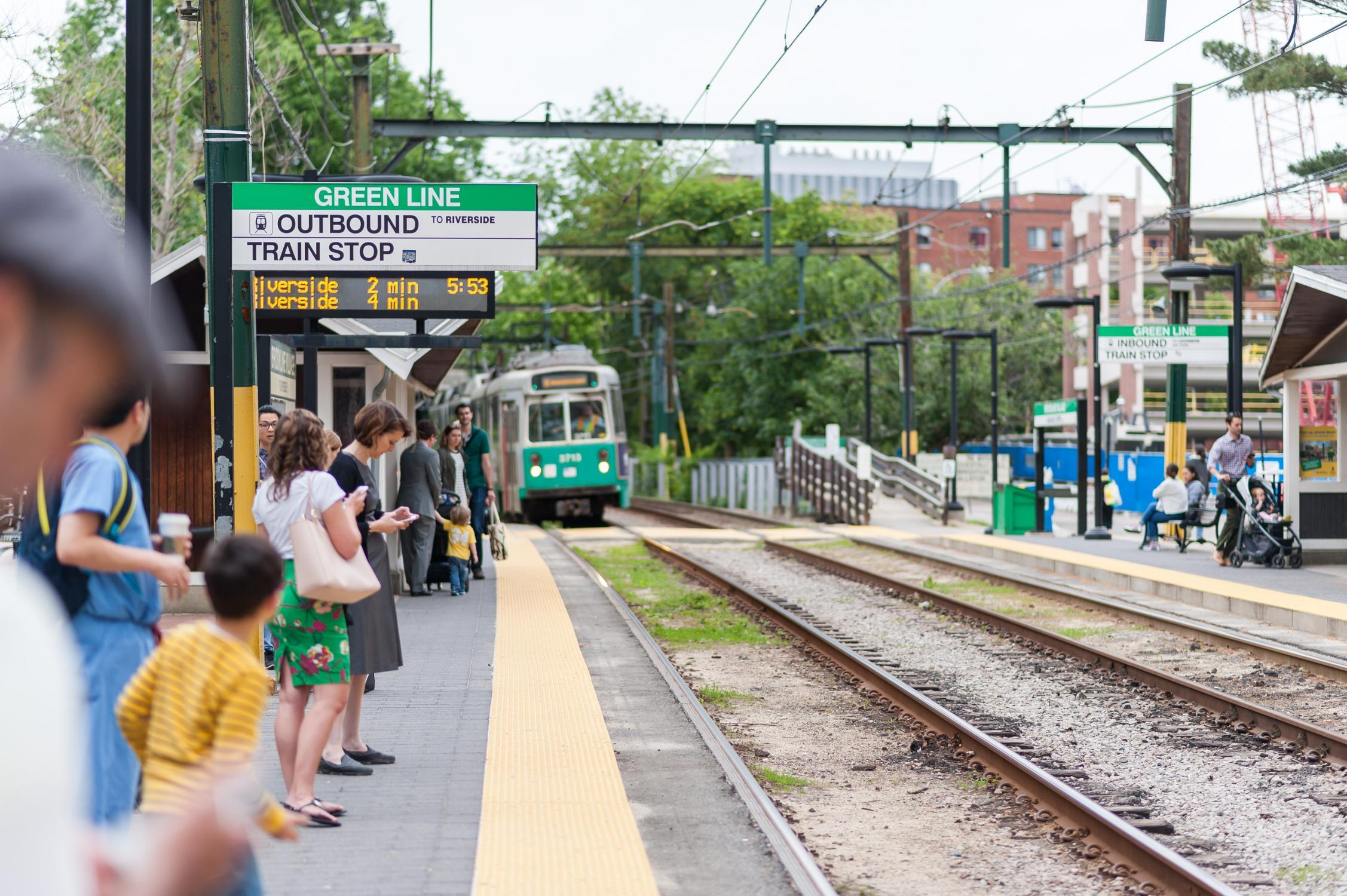Riders wait on the platform at the Brookline Village stop on the Green Line D branch
