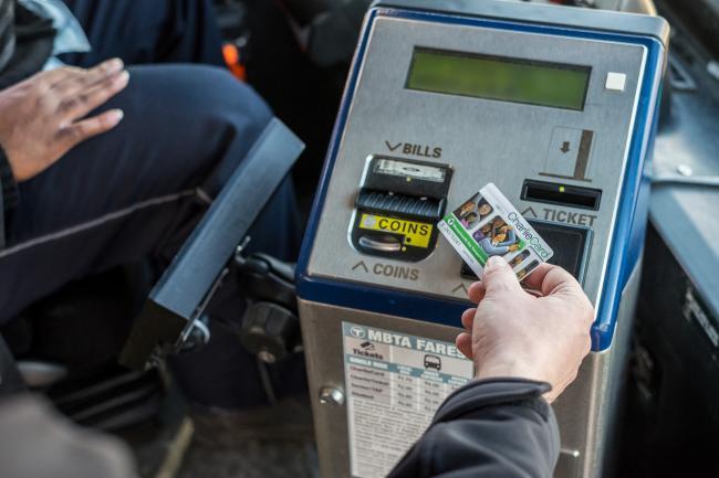 A rider taps his CharlieCard on a farebox while boarding the bus