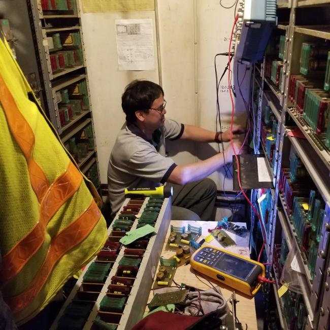Inside the JFK/UMass signal house, a technician crouches among the signals to make repairs, with a safety vest and other equipment in the foreground