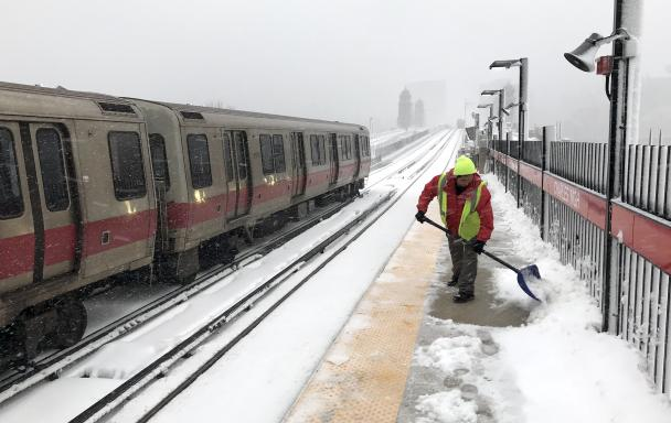 A crewman clears snow from the MGH platform