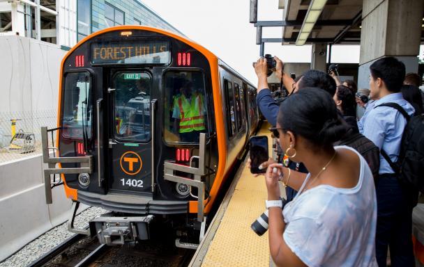 New Orange Line car at Wellington, as a crowd on the platform takes photos.