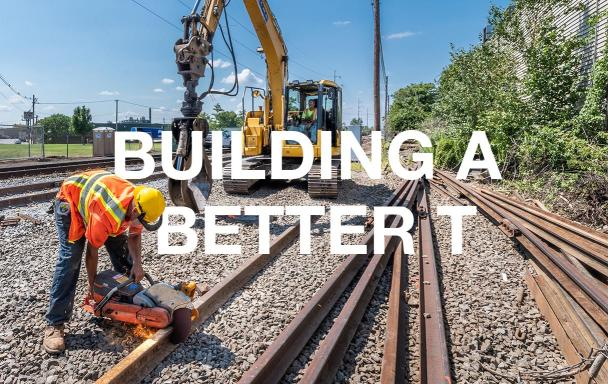 "A crewperson in the foreground cuts rail while another crewperson sits in heavy machinery in the bakground. White text overlaid reads ""Building a Better T."""