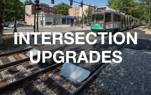 "A closeup of an upgraded intersection, with a Green Line C train approaching. White text overlaid reads ""Intersection Upgrades."""