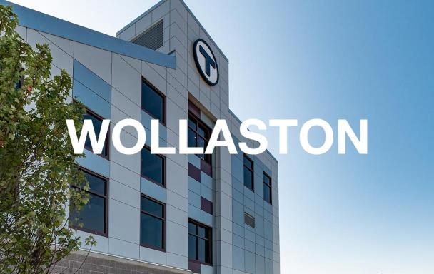 "The facade of the newly rebuilt Wollaston Station, with white text overlaid that reads ""Wollaston"""