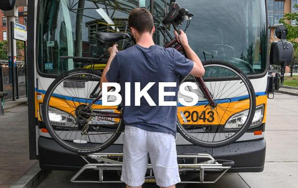 "Overlaid text reads ""Bikes."" A rider mounts his bike on a bus bike rack."