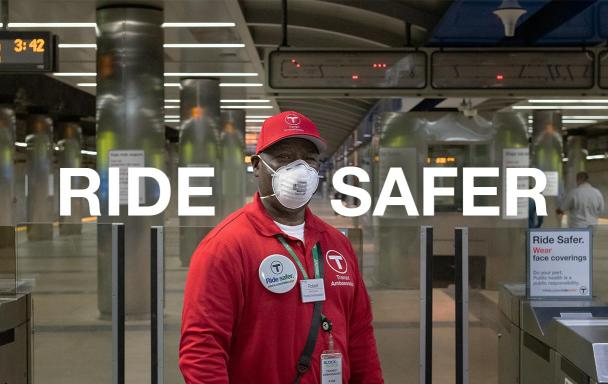 "Text overlaid reads ""Ride Safer."" T Ambassador with a mask stands at the fare gates at Maverick Station."